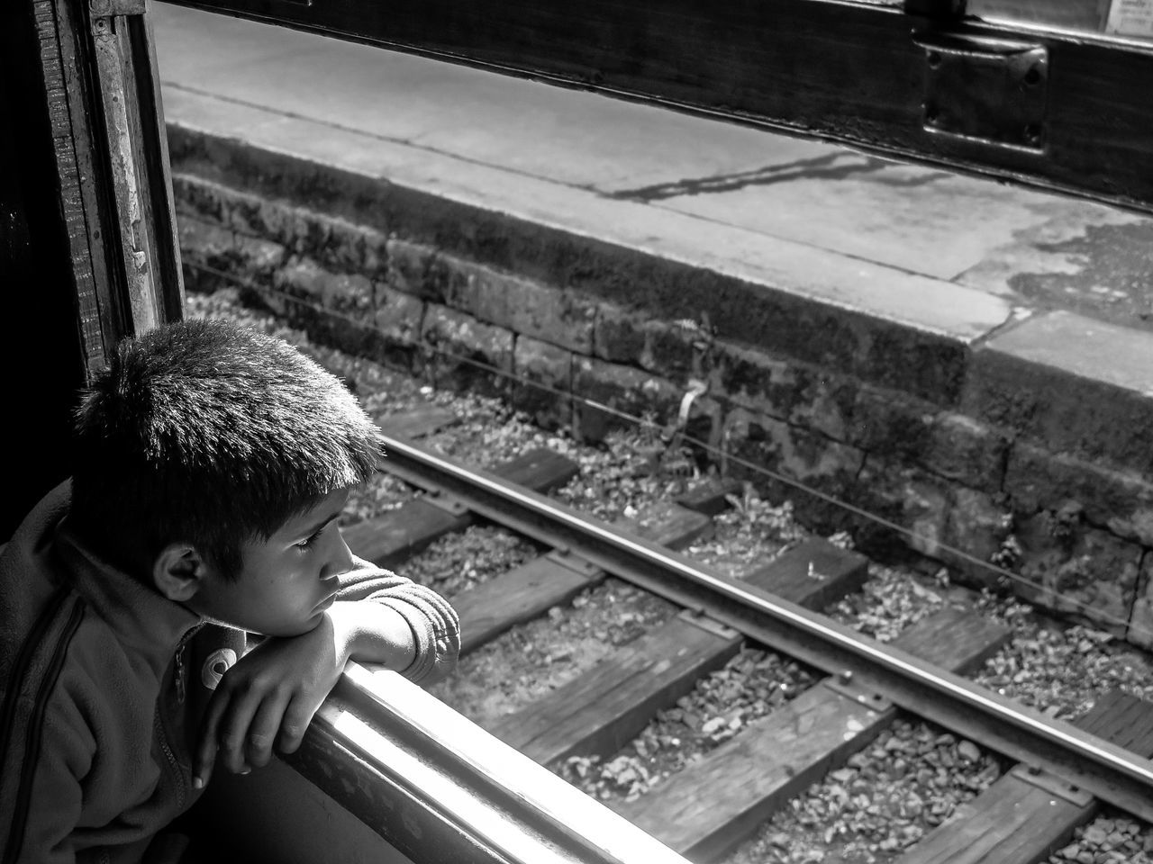 Black And White Boys Childhood Day Elementary Age High Angle View Indoors  Kid Lifestyles Looking Monochrome One Person People Rail Transportation Railroad Track Real People Sitting Sri Lanka Train Train Station Transportation Travelling Vintage Wagon  Window