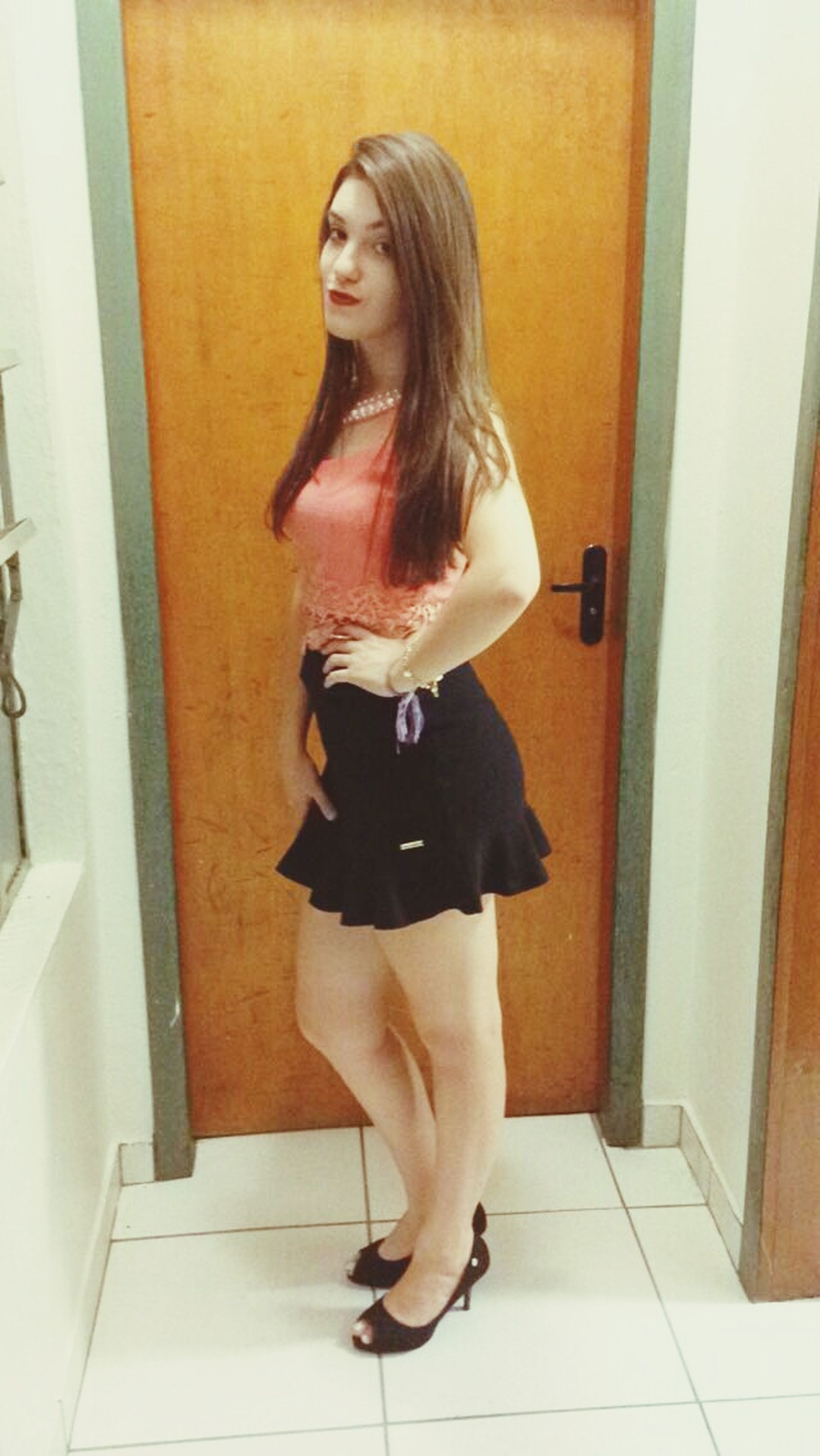 indoors, full length, young adult, lifestyles, young women, home interior, person, casual clothing, leisure activity, door, long hair, standing, domestic room, front view, three quarter length, looking at camera, sitting