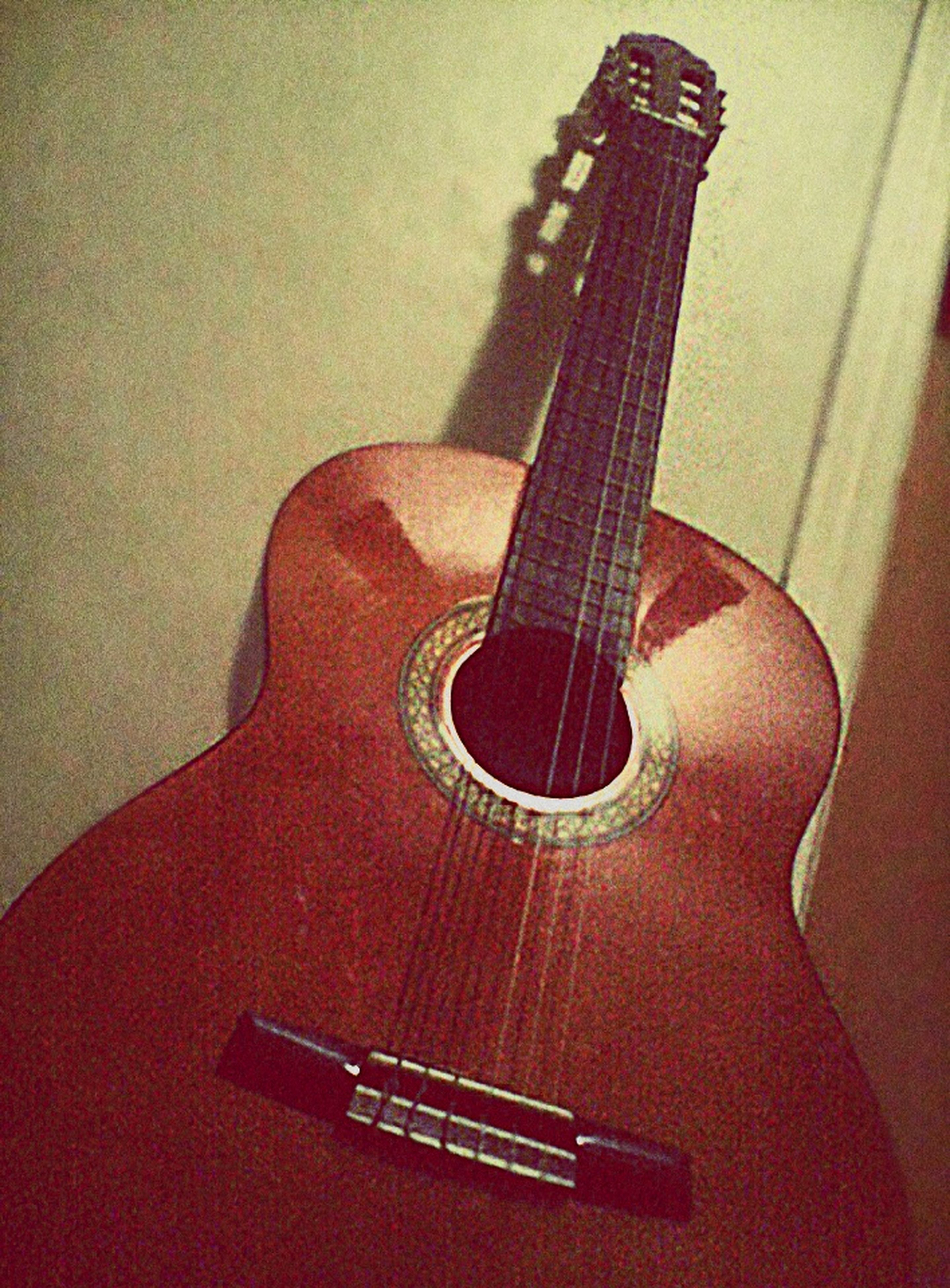 musical instrument, music, guitar, musical instrument string, musical equipment, arts culture and entertainment, indoors, string instrument, close-up, single object, acoustic guitar, still life, metal, no people, wall - building feature, selective focus, metallic, wood - material, equipment, high angle view