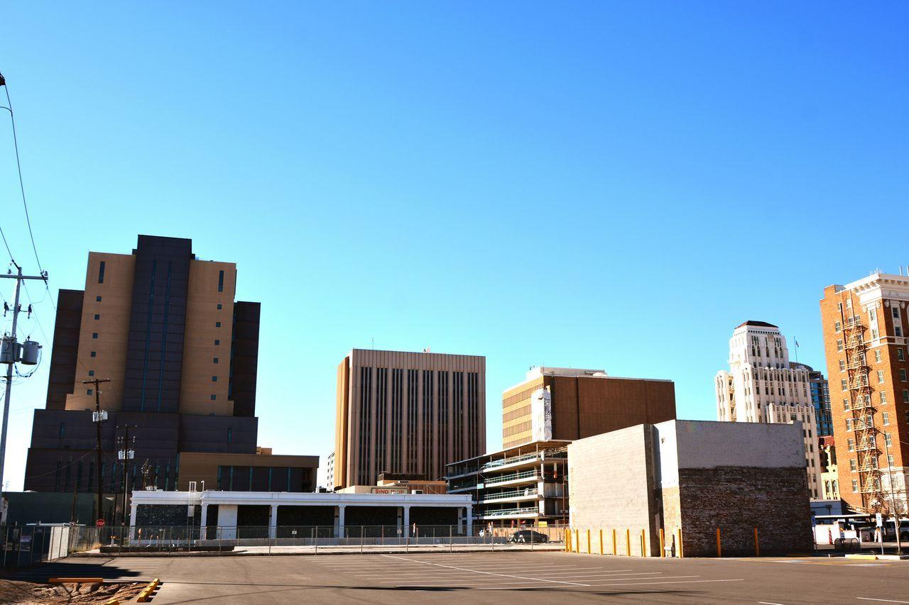 Exterior Of City Buildings Against Clear Blue Sky