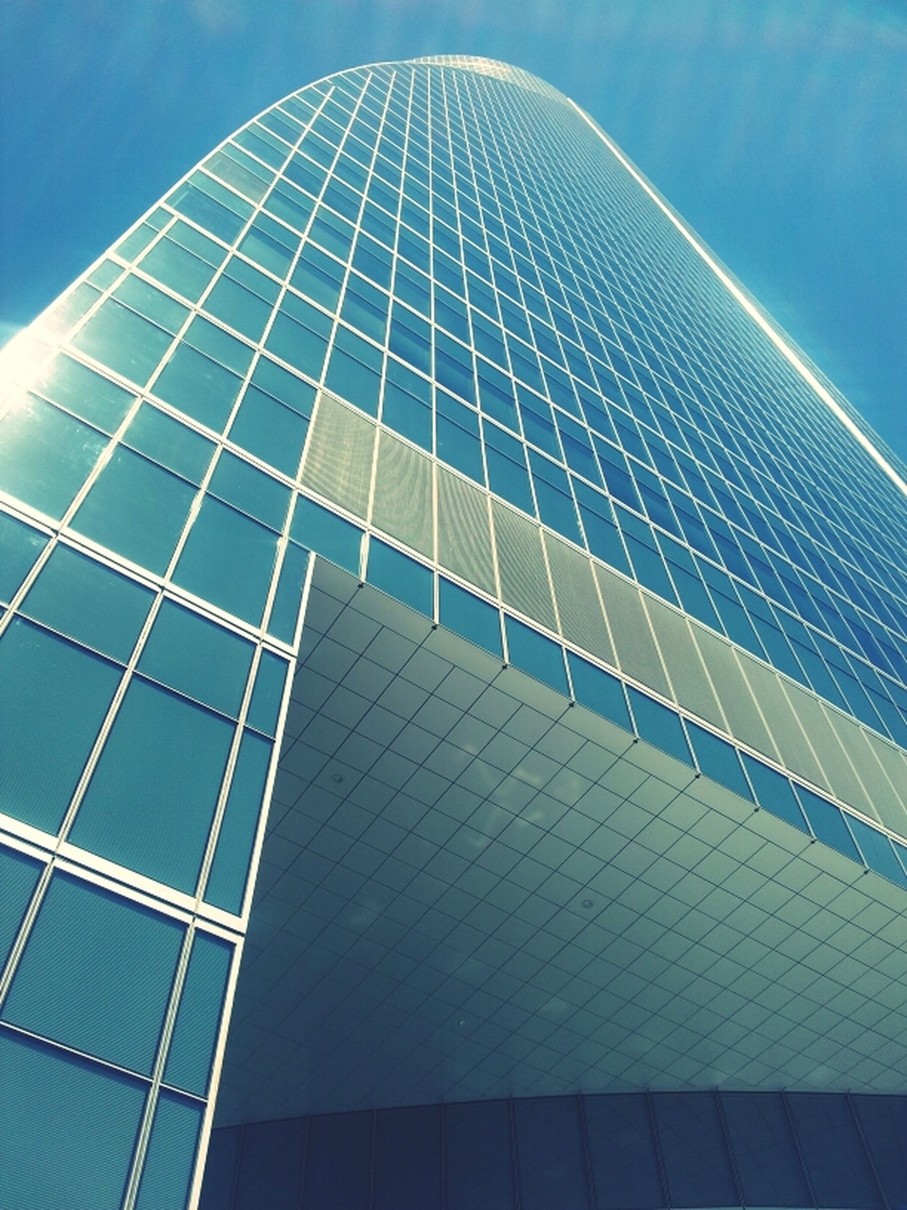 low angle view, architecture, built structure, modern, building exterior, office building, blue, skyscraper, tall - high, glass - material, sky, city, tower, reflection, pattern, building, day, architectural feature, outdoors, no people