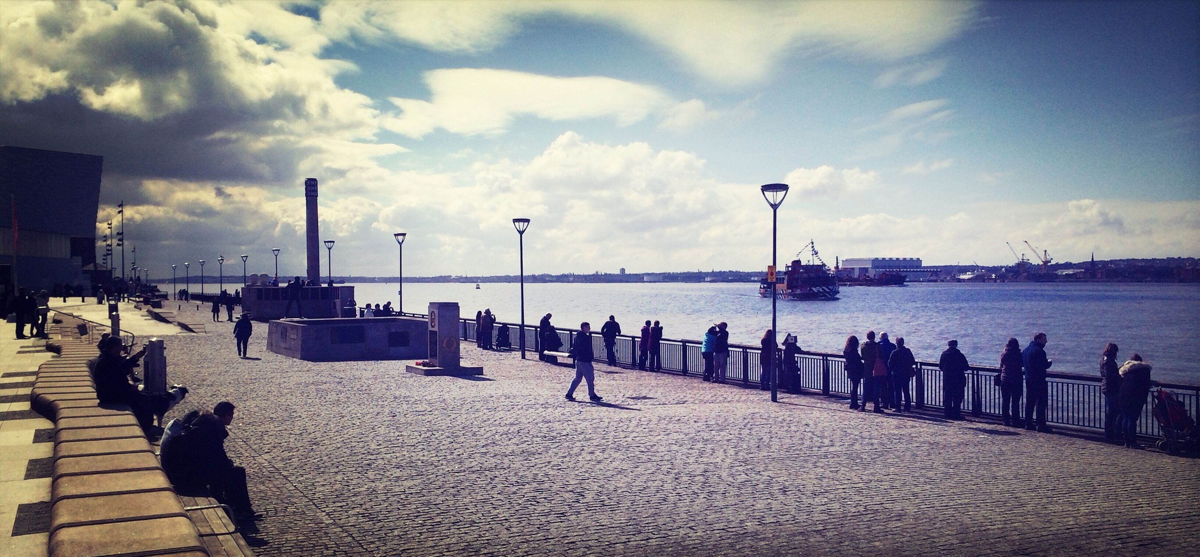 sky, sea, water, beach, cloud - sky, built structure, pier, architecture, shore, cloud, incidental people, tranquility, in a row, sand, nature, street light, tranquil scene, building exterior, cloudy, scenics