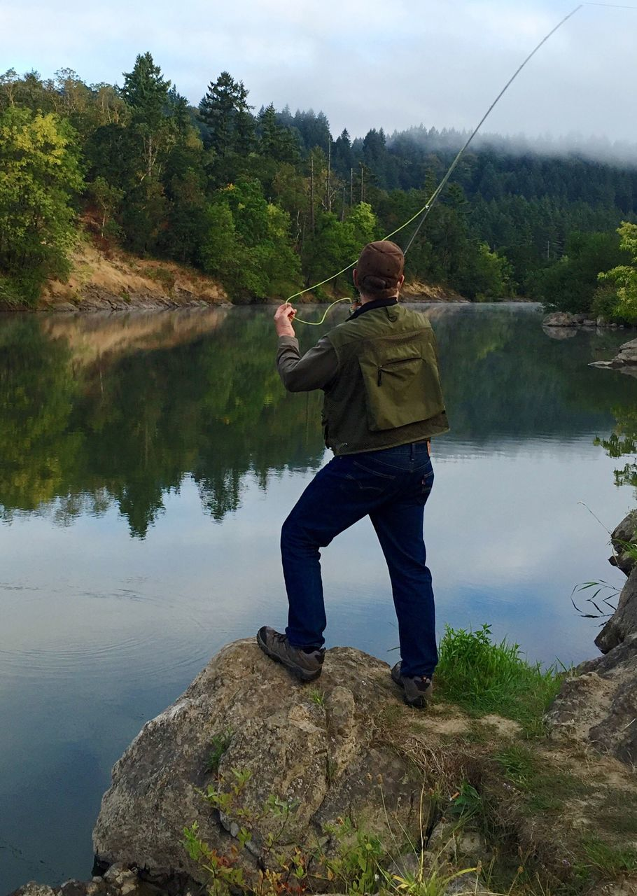 water, real people, fishing, one person, lake, nature, standing, full length, tree, day, leisure activity, outdoors, fishing pole, fishing tackle, sky, beauty in nature