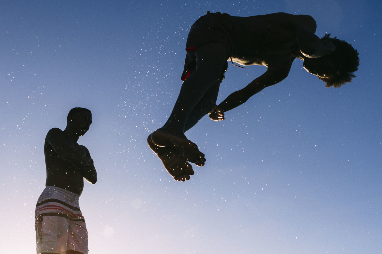 Low Angle View Of Silhouette Person Jumping Against Clear Sky