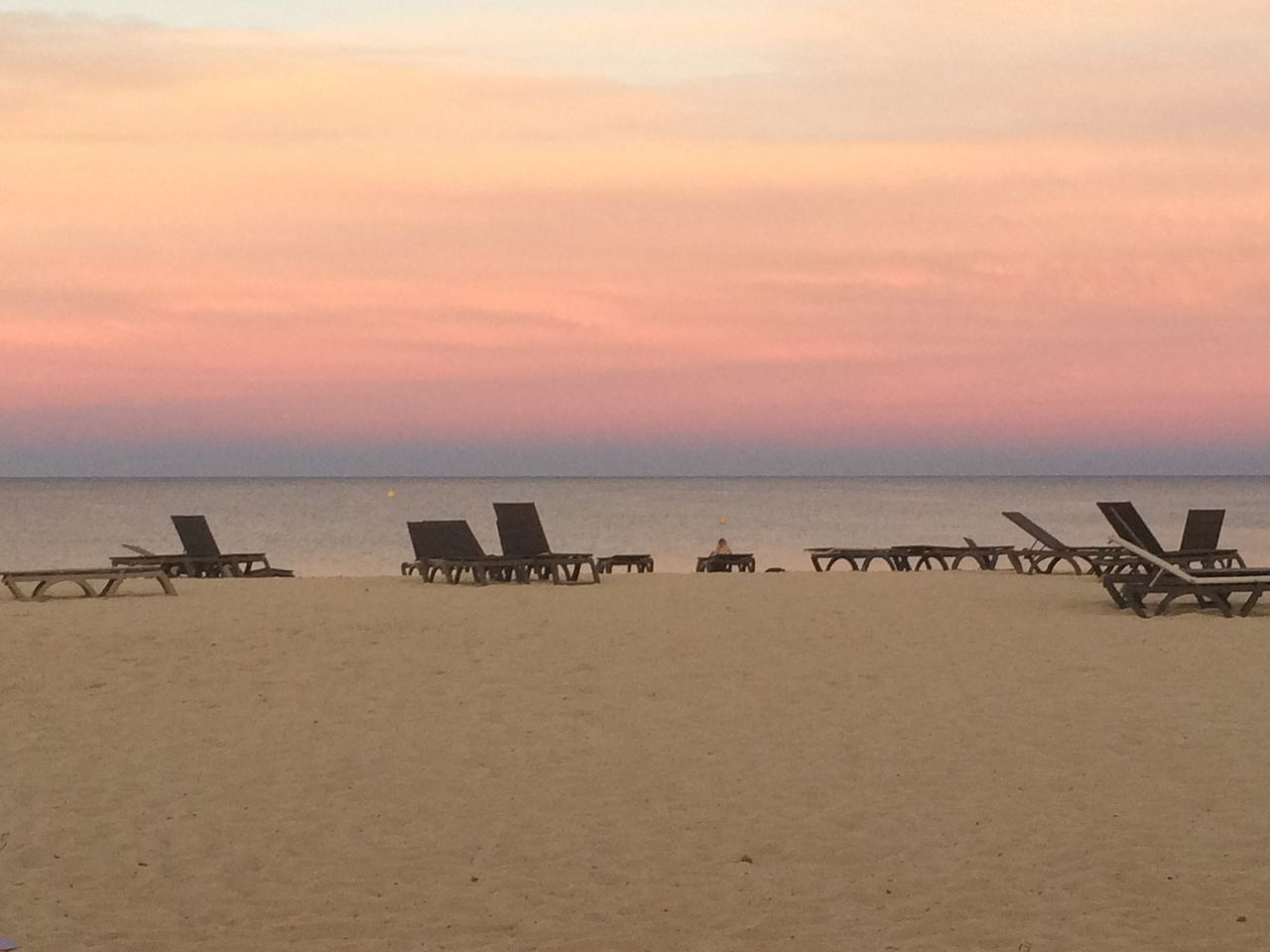 Empty Deck Chairs On Sand At Beach Against Pink Sky During Sunset