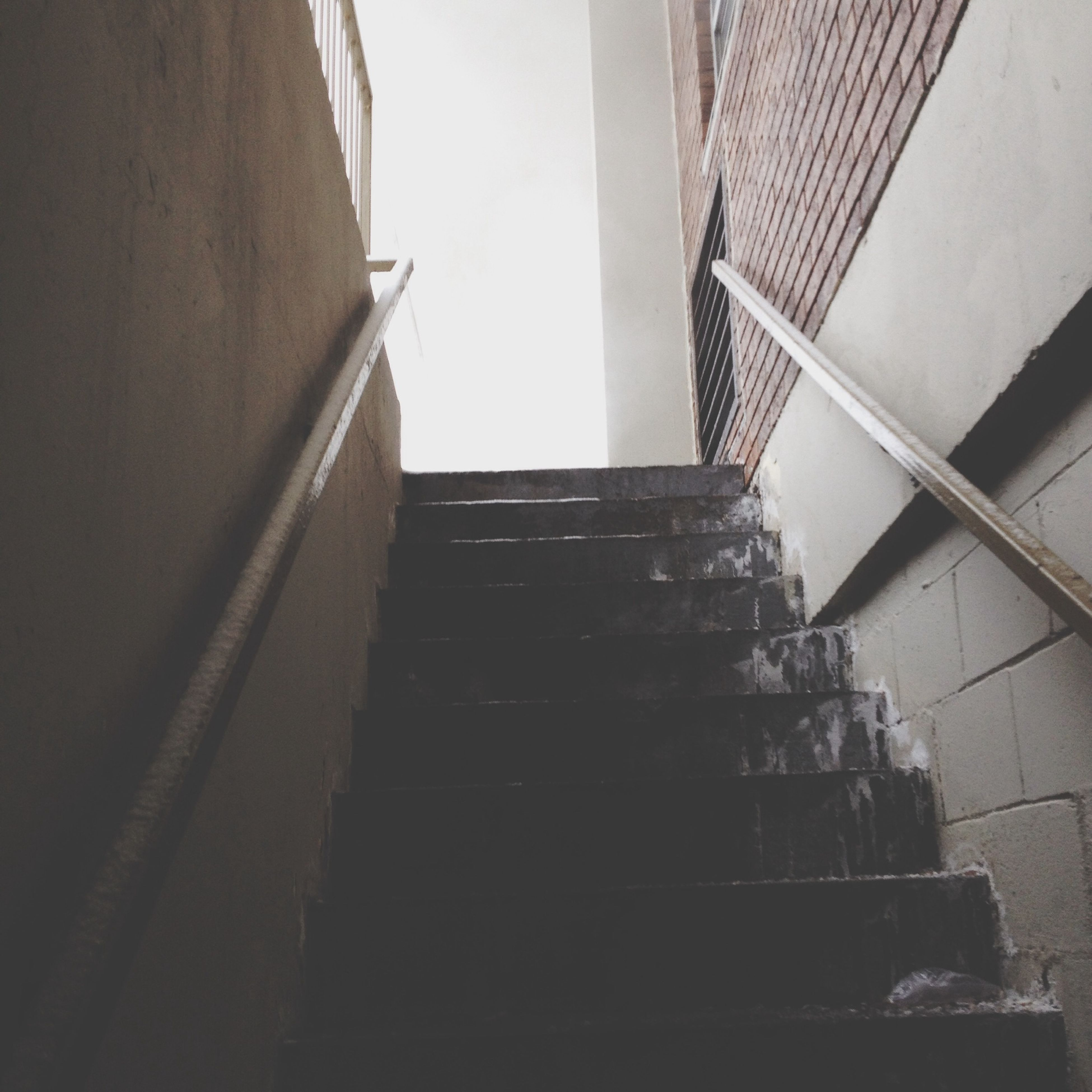 low angle view, architecture, built structure, staircase, steps and staircases, steps, building exterior, building, railing, wall - building feature, indoors, stairs, directly below, no people, sunlight, day, wall, clear sky, the way forward, brick wall