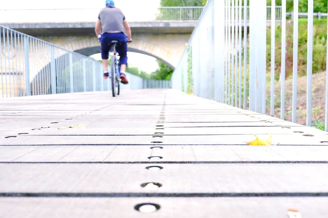 Unabridged Bicycle The Way Forward Transportation Land Vehicle Motion Rear View Mode Of Transport Bridge - Man Made Structure Selective Focus Day Growth Pedestrian Walkway Surface Level Footbridge Person Outdoors Narrow Wood Paneling Eye4photography  Phootooftheday Picoftheday