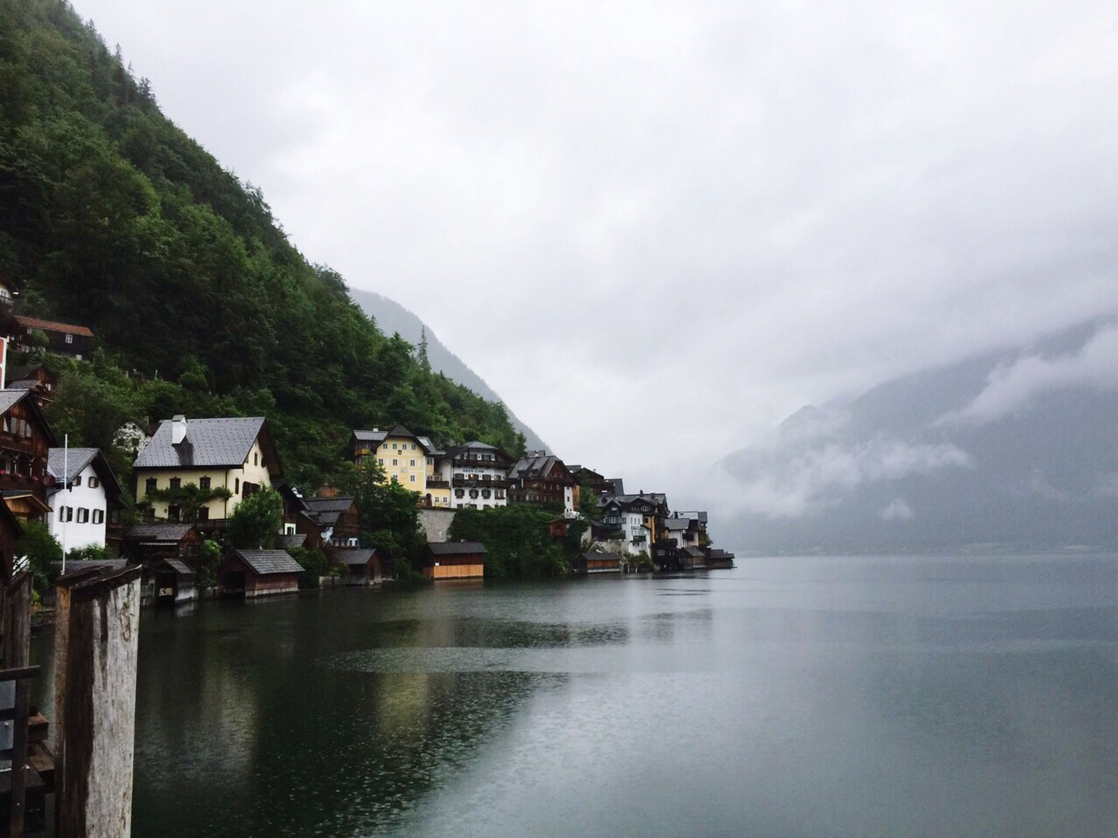 building exterior, architecture, built structure, water, mountain, sky, house, waterfront, residential structure, town, sea, residential building, residential district, tree, townscape, nature, scenics, cloud - sky, day, tranquil scene
