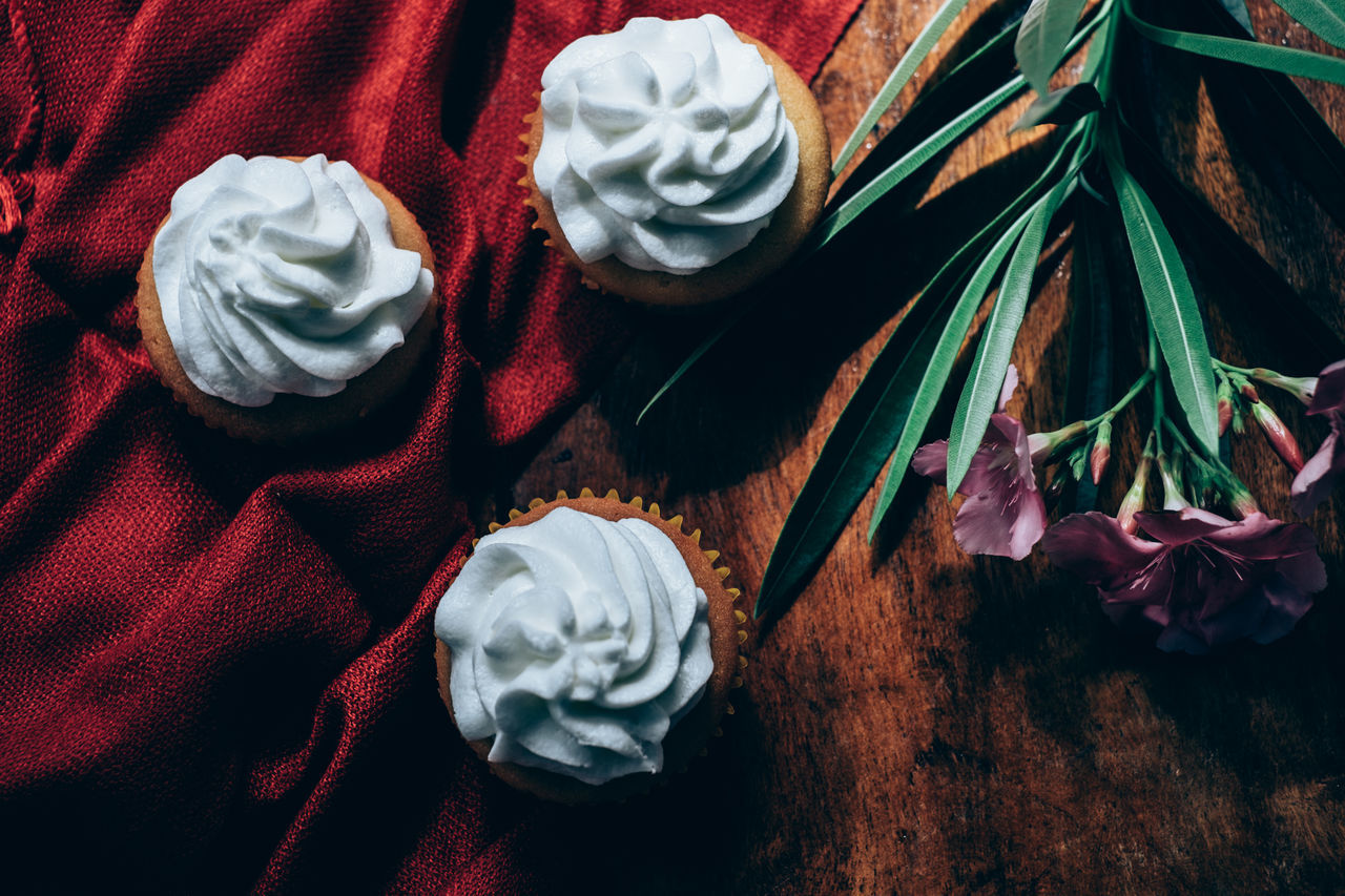 Vanilla cupcakes on wooden table Adelfa Close-up Cupcakes Day Dessert Flat Lay Flower Flower Head Food Food And Drink Freshness High Angle View Ice Cream Icing Indoors  Indulgence Muffin Red Still Life Sweet Food Table Top View Vanilla Visual Feast Wood - Material