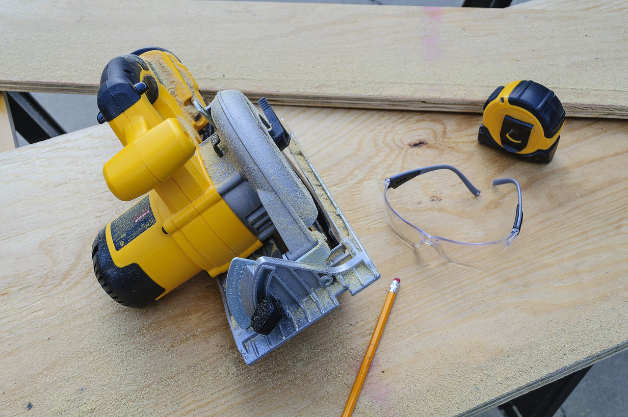 Yellow Circular Saw, Tape Measure and Safety Glasses on Wood Board Blade Board Circular Saw Equipment Gear Hand Tools Handyman Power Tools Rotary SafetyGlasses Saw Tape Measure Tools Wood