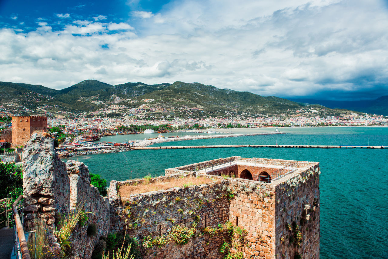 View of The Kizil Kule (Red Tower) is a historical tower in the Turkish city of Alanya Ancient Architecture Building Exterior Castle Cloudy Day Defensive Structure Fortification Fortress Harbor Kızıl Kule Landscape Medieval Architecture Middle East Mountains Nature No People Outdoors Red Tower Sky Symbol Tower Travel Destinations Turkey Turkish Riviera Turquoise Water Water