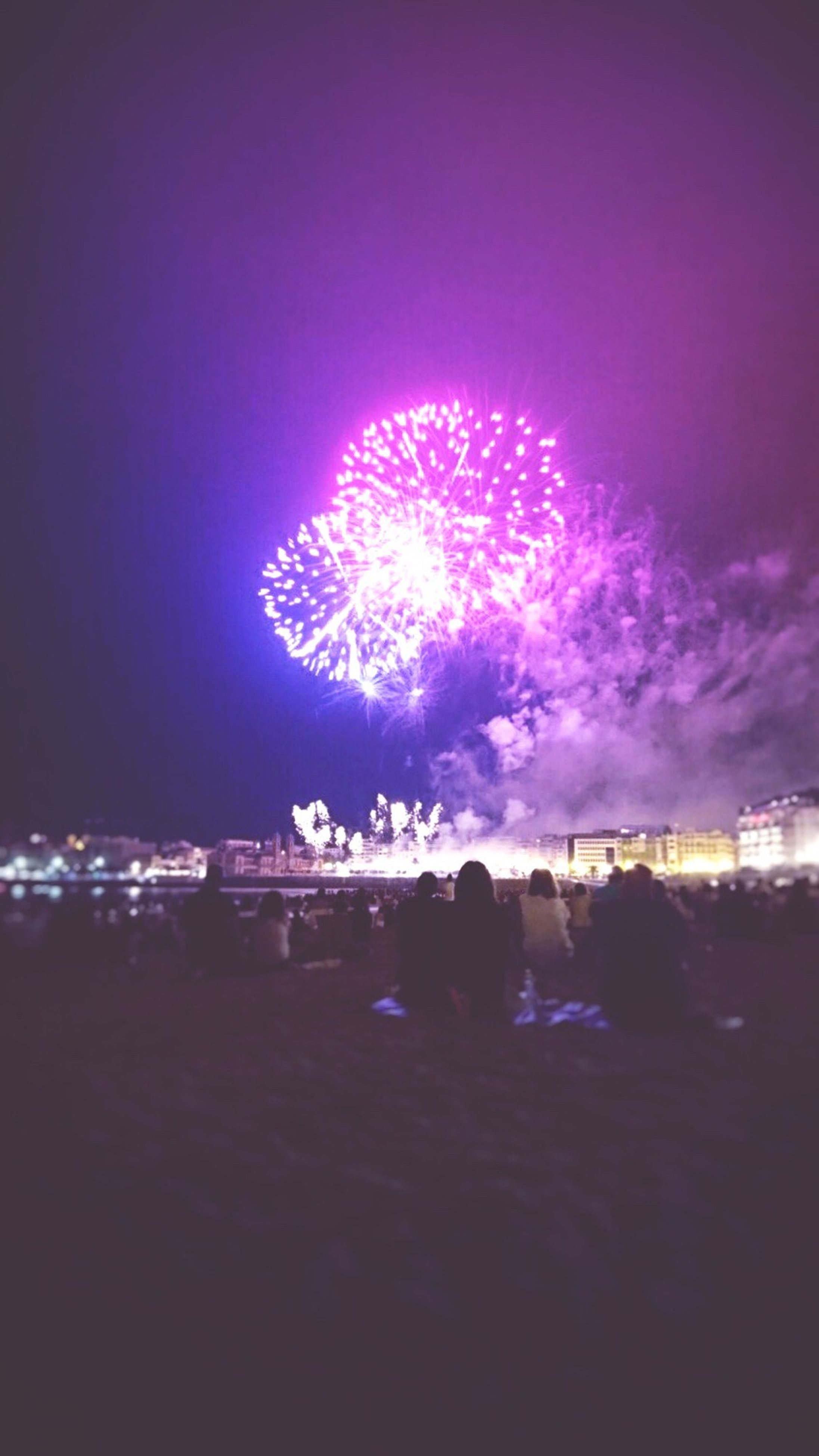 illuminated, night, celebration, firework display, glowing, exploding, sparks, firework - man made object, city life, sky, event, outdoors, dark, person, entertainment