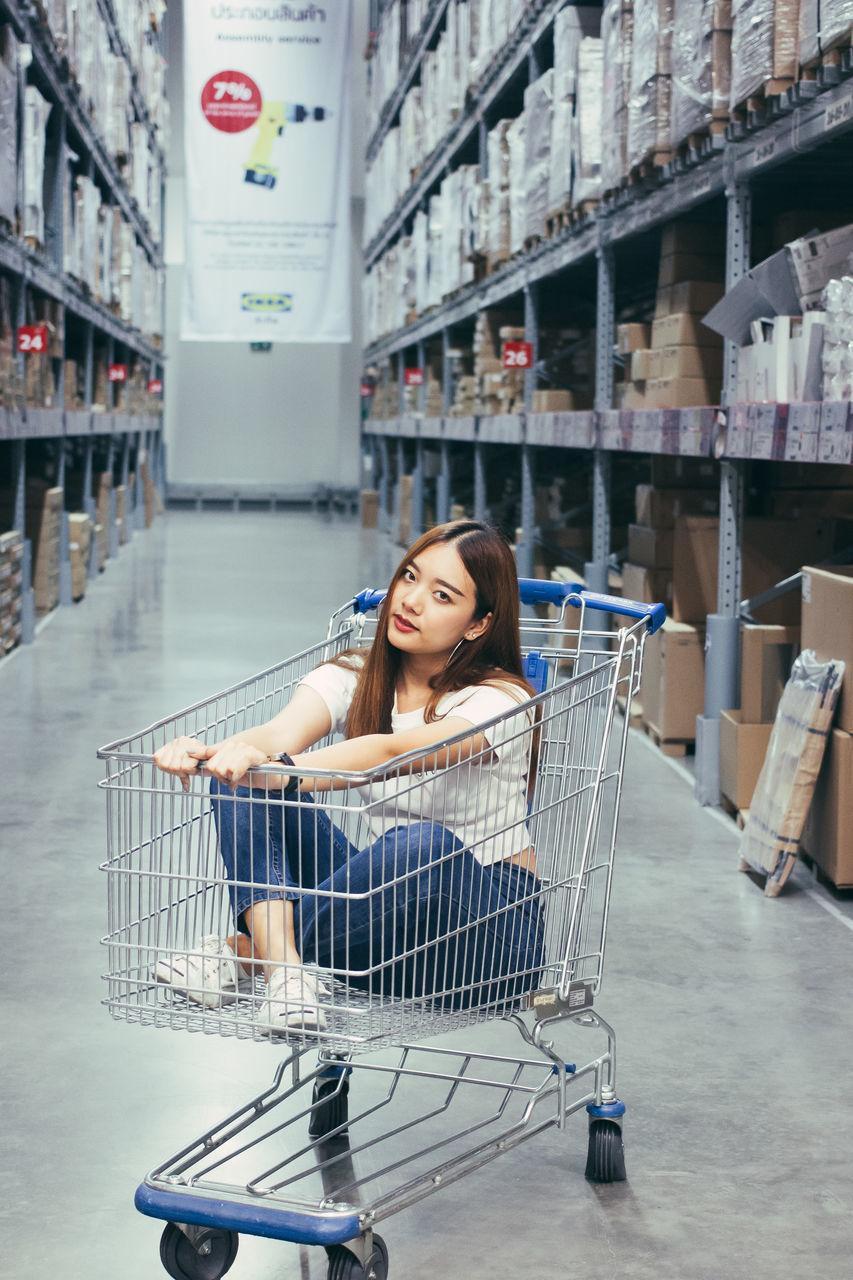 one person, full length, shopping cart, consumerism, sitting, young adult, lifestyles, young women, real people, indoors, day, portrait, one young woman only, supermarket, people