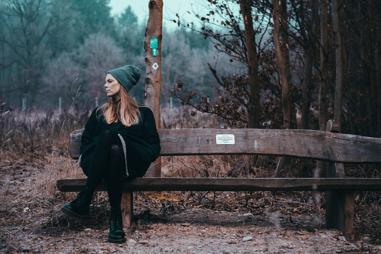 tree, one person, young adult, front view, real people, full length, young women, outdoors, leisure activity, sitting, tree trunk, nature, day, lifestyles, forest, bare tree, beautiful woman, warm clothing, sky, adult, people