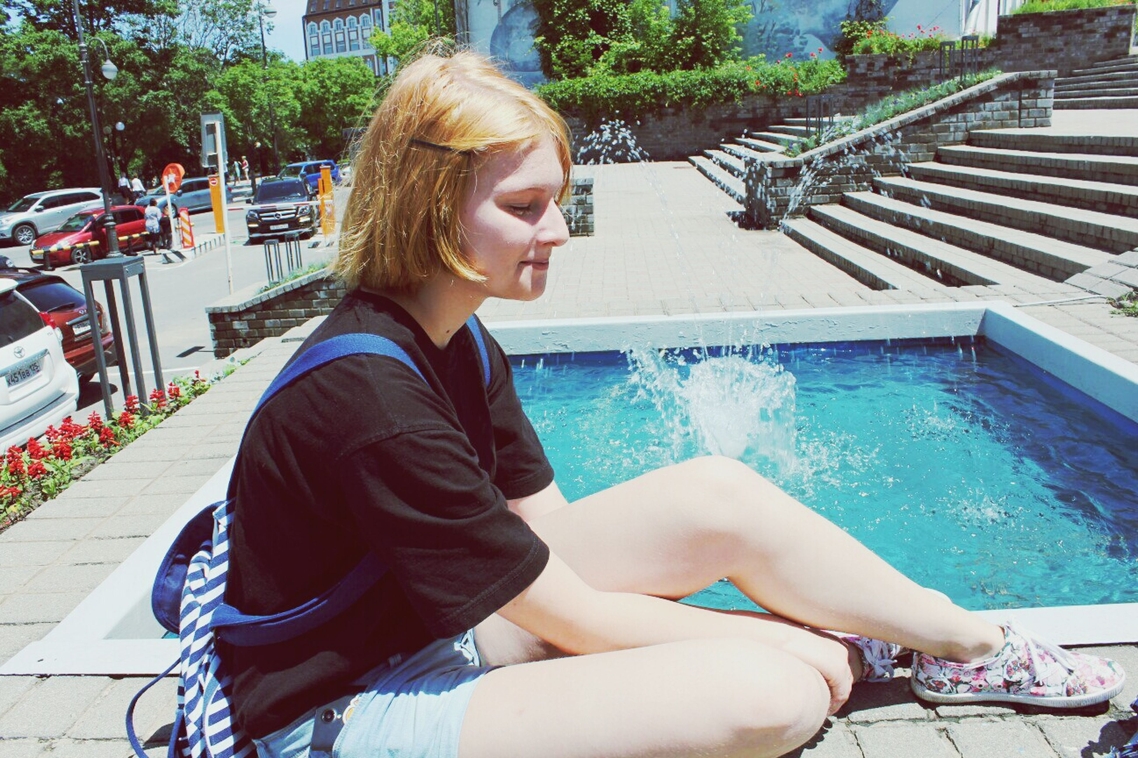 person, lifestyles, young adult, casual clothing, leisure activity, building exterior, built structure, architecture, looking at camera, young women, portrait, sunglasses, water, front view, three quarter length, sitting, smiling, standing