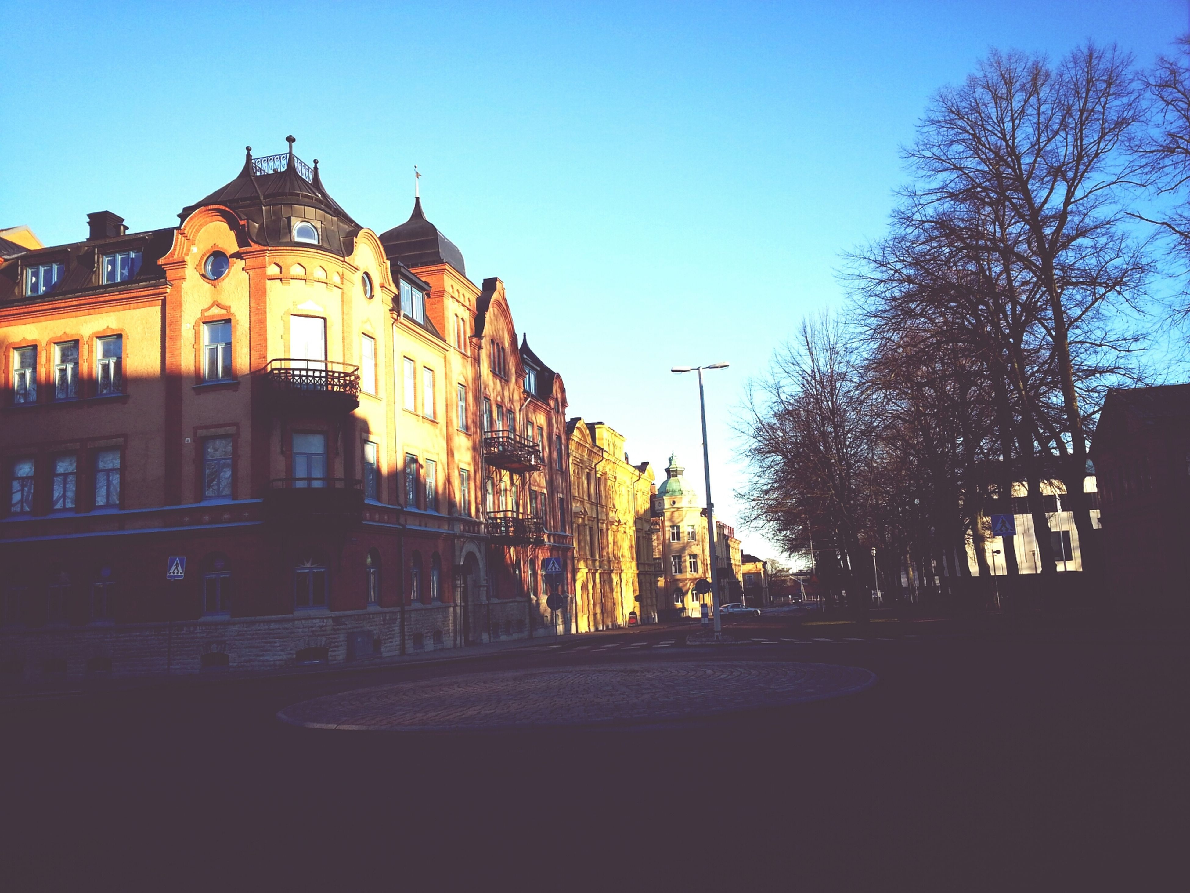 building exterior, architecture, built structure, clear sky, illuminated, blue, tree, copy space, city, dusk, sky, building, residential structure, street light, residential building, house, outdoors, sunset, night, street
