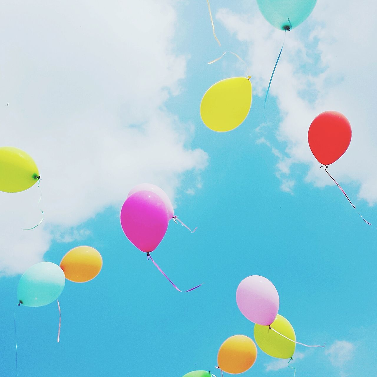 balloon, celebration, helium balloon, multi colored, helium, mid-air, low angle view, flying, party - social event, sky, celebration event, birthday, cloud - sky, yellow, outdoors, day, childhood, fragility, no people, ballooning festival, releasing, hot air balloon