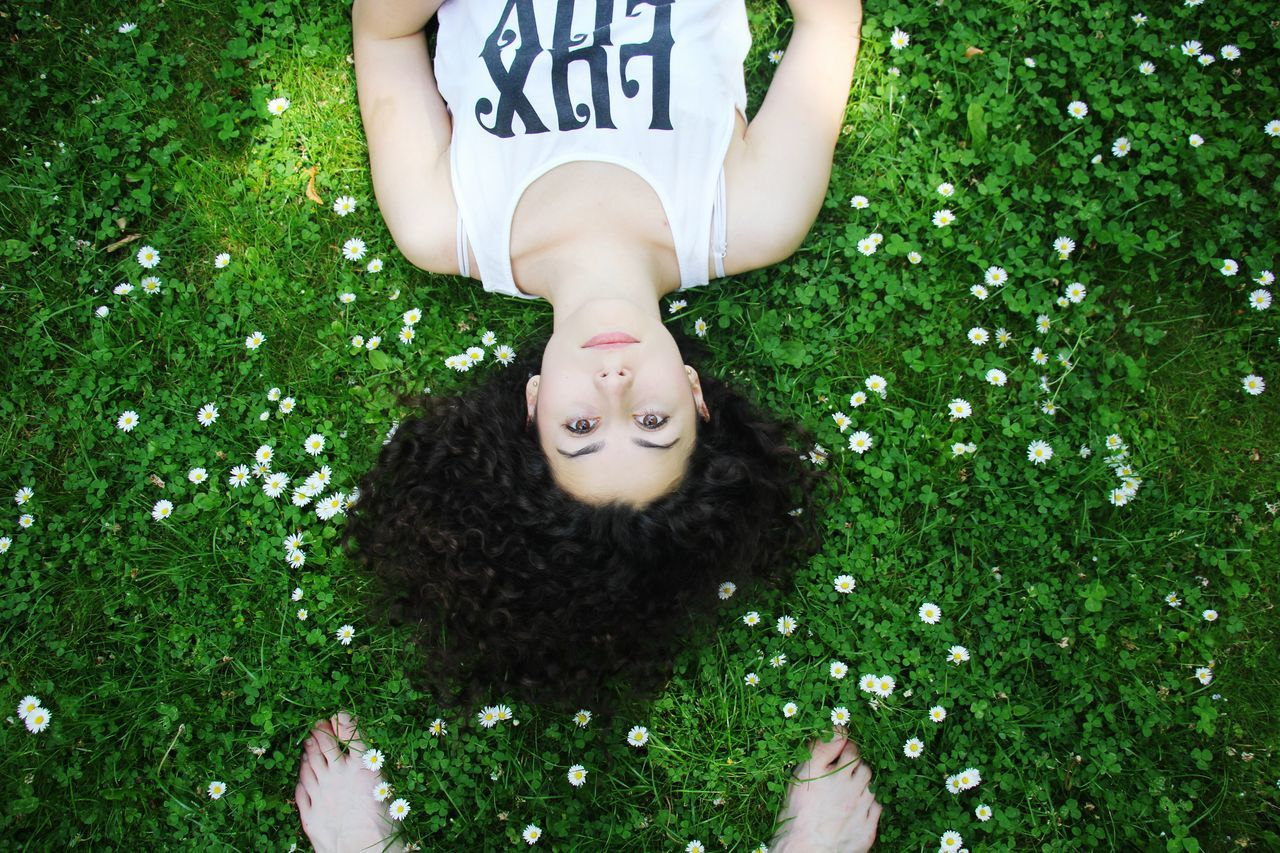 one person, grass, directly above, low section, high angle view, real people, outdoors, day, pets, lying down, human body part, domestic animals, animal themes, mammal, people, human leg, adult
