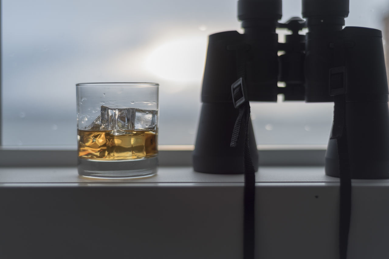 Whiskey on ice with binoculars windowsill. Alcohol Beverage Binoculars Brandy Close-up Day Dram Drink Drinking Glass Masculine No People Outdoors Refreshment Snifter Social Issues Table Whiskey Window
