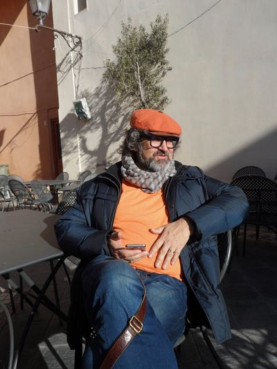 Relaxing in the sun, in Italy, mobile at the ready. Relaxing With Mobile In The Sunlight Contemplating Beard Cap Sitting Outside Real People Outdoors Adult Day Orange Color orange clothes Orange Clothes Orange Cap