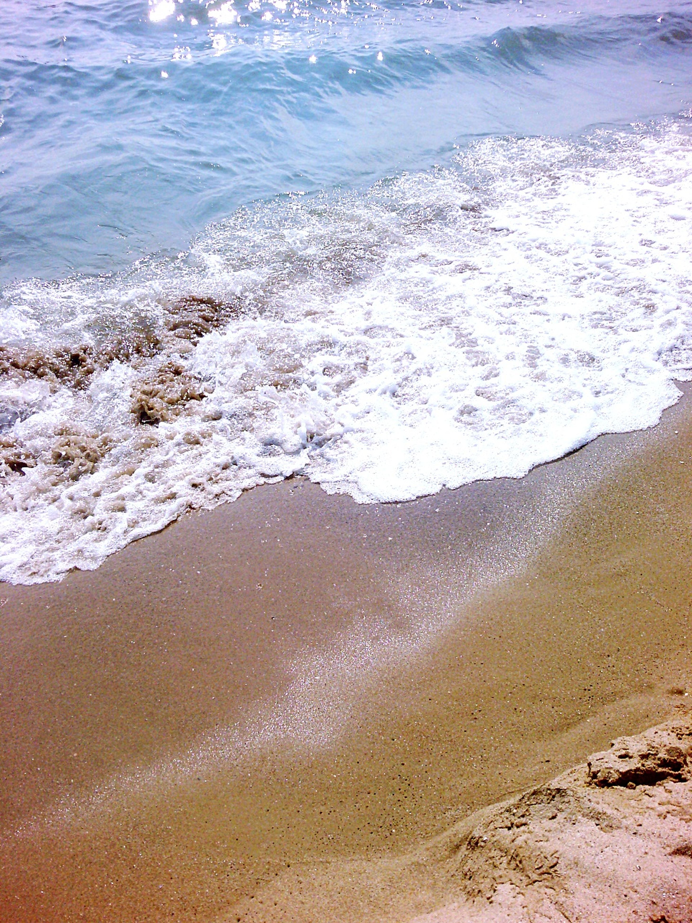 water, beach, sea, sand, shore, tranquility, wave, tranquil scene, surf, beauty in nature, scenics, nature, coastline, high angle view, idyllic, outdoors, day, horizon over water, sunlight, no people