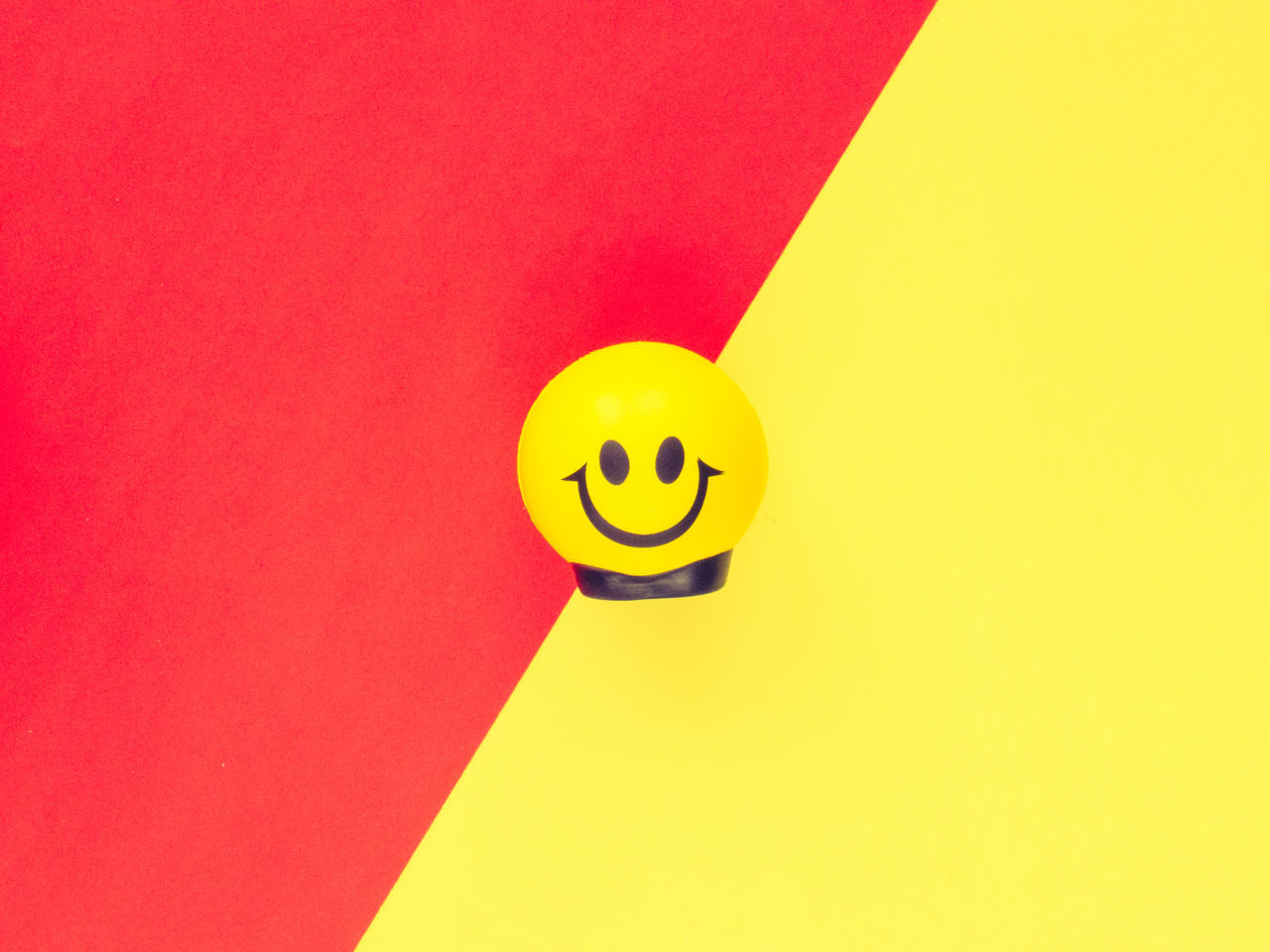 Smiling stress ball on a colorful pastel background. Anthropomorphic Smiley Face Ball Calm Circle Color Contrast Emoji Emotions Happiness Indoors  Minimalism No People Object Ofice Pattern Red Still Life Stress Stress Ball Yellow