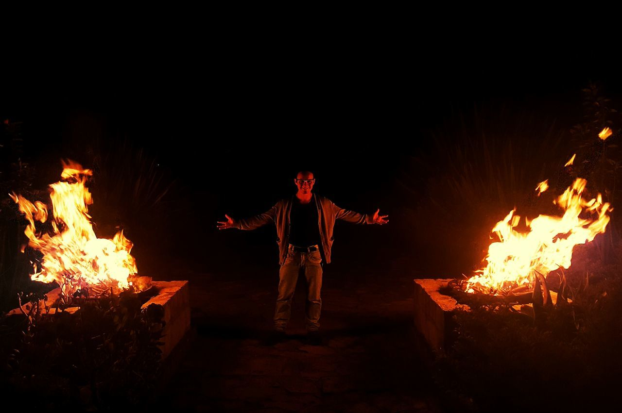 fire - natural phenomenon, flame, burning, night, heat - temperature, campfire, bonfire, real people, fire, glowing, leisure activity, motion, full length, one person, front view, danger, young men, outdoors, fire pit, standing, men, young adult, nature, people