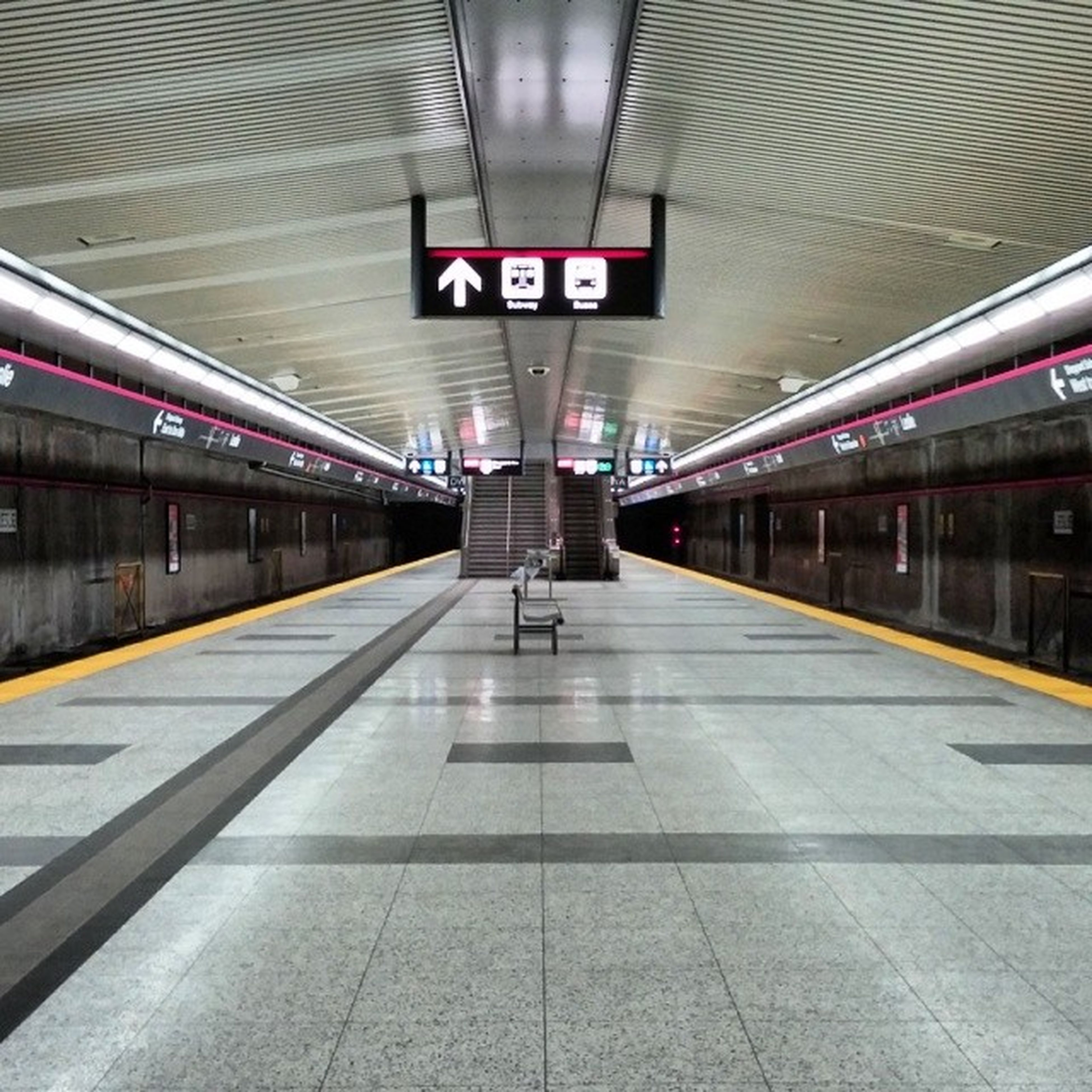 indoors, railroad station, subway station, railroad station platform, public transportation, ceiling, subway, transportation, rail transportation, illuminated, interior, transportation building - type of building, empty, architecture, subway platform, travel, built structure, text, flooring, station