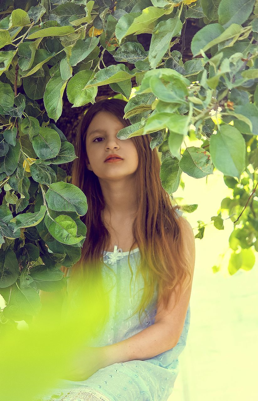 Portrait Of Girl Sitting By Tree At Yard