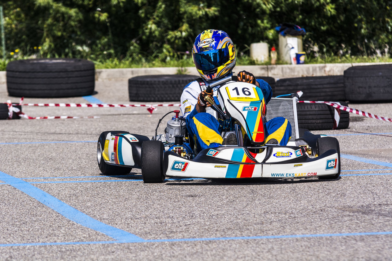 portrait of a go kart at a public event held in a parking lot Auto Racing Competition Crash Helmet Day Headwear Motor Racing Track Motorcycle Racing Motorsport Outdoors People Racecar Speed Sport Sports Race