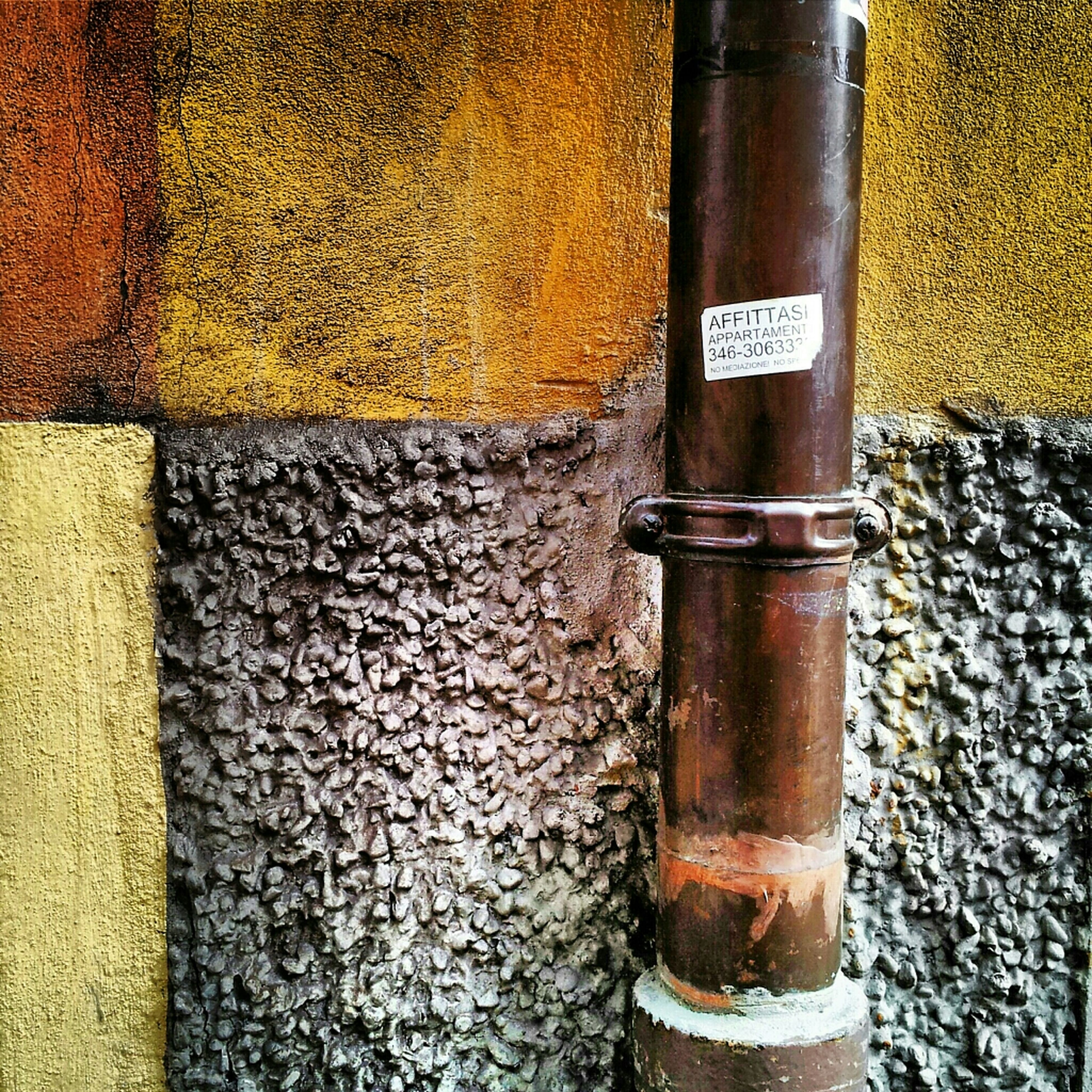 metal, close-up, communication, text, no people, day, yellow, rusty, wall - building feature, outdoors, built structure, metallic, street, western script, architecture, sidewalk, building exterior, old, protection, high angle view
