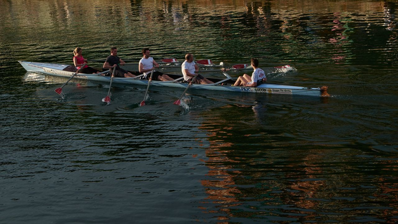 nautical vessel, transportation, rowing, oar, nature, water, outdoors, day, mode of transport, medium group of people, rowboat, river, men, leisure activity, sitting, women, tree, sculling, togetherness, young adult, real people, sport rowing, young women, scull, adult, people, adults only