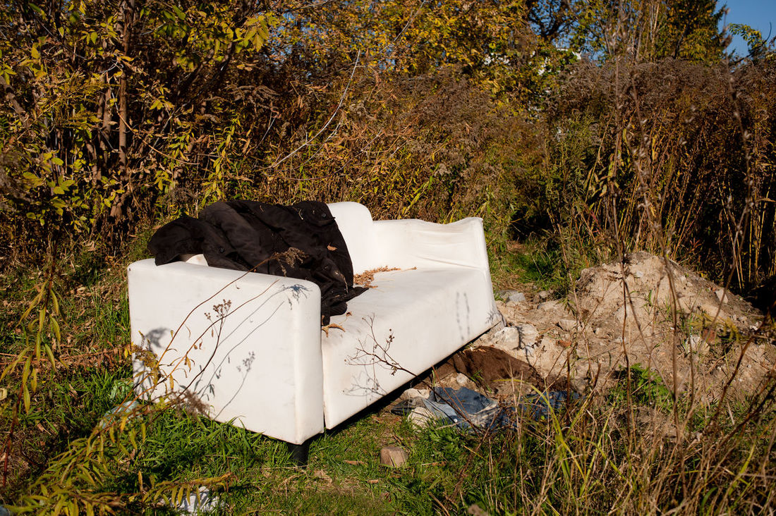 One white old used sofa garbage discarded outdoors in meadow full of grown dried plants on the ground in Poland, horizontal orientation, nobody. Abandoned Aged Cracked Damaged Dilapidated Discarded Dispose Dump Expendables Furniture Garbage Junk Nature No People Obsolete Old Outdoors Redundant Rubbish Shed Sofa Thrown Away Trash Waste Weathered