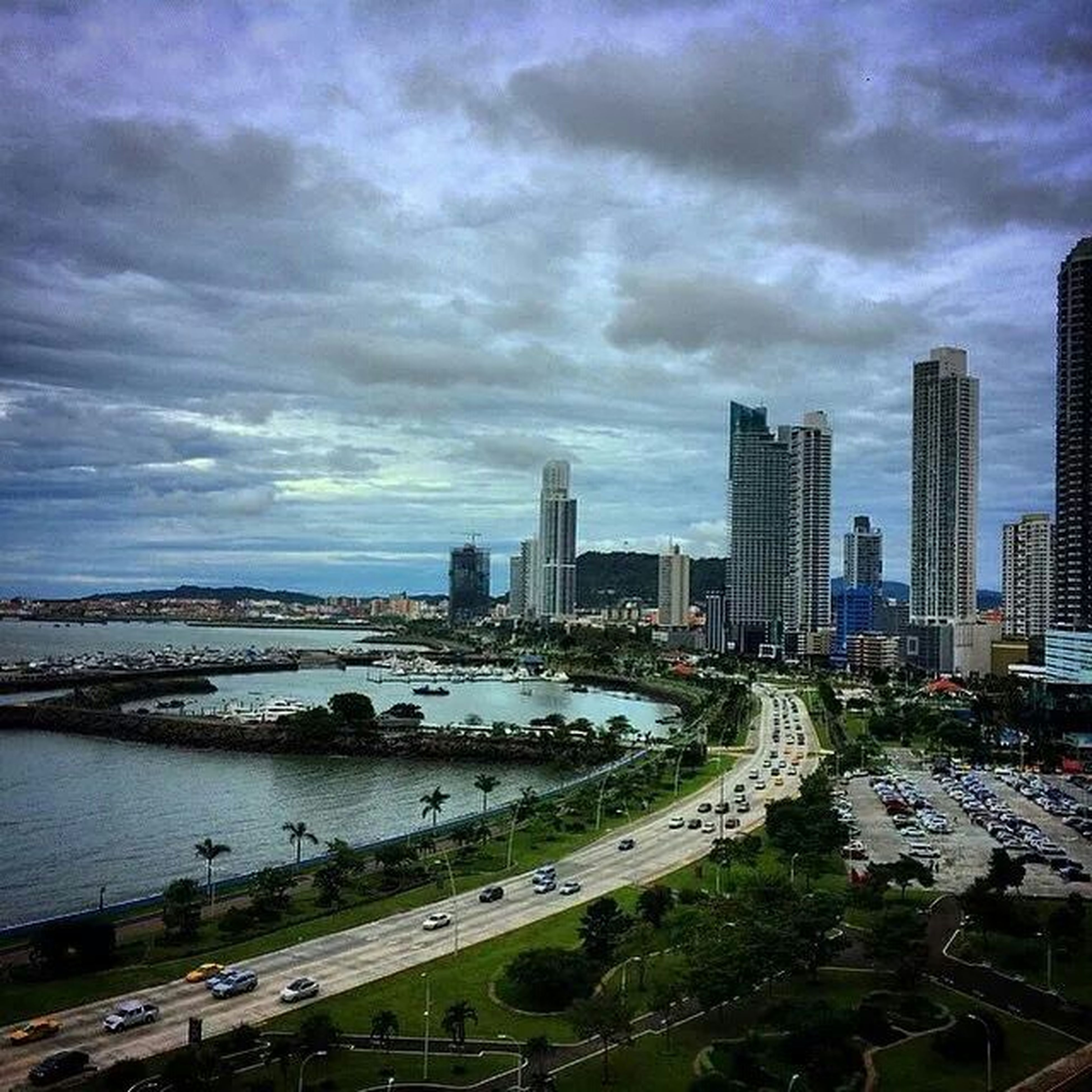 city, architecture, building exterior, cityscape, built structure, skyscraper, sky, water, river, cloud - sky, urban skyline, tower, modern, tall - high, skyline, capital cities, city life, cloudy, office building, bridge - man made structure