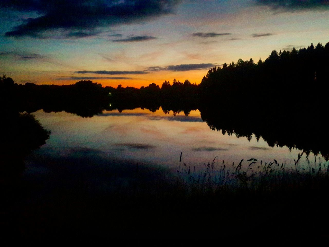 sky, silhouette, cloud - sky, sunset, nature, scenics, tranquil scene, lake, beauty in nature, reflection, tranquility, water, outdoors, dusk, landscape, tree, no people, growth, travel destinations, plant, grass, day