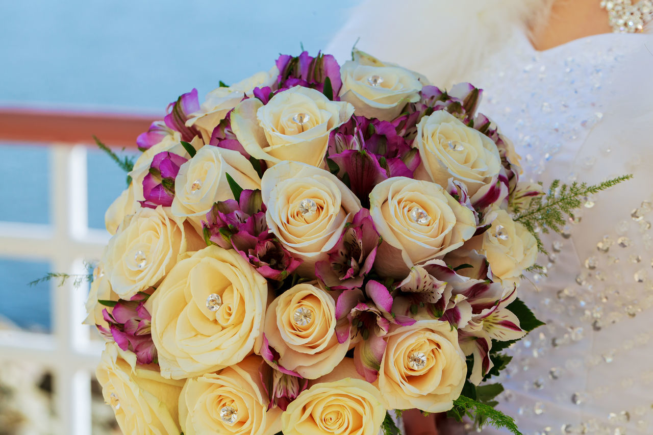 Midsection Of Bride With Rose Bouquet