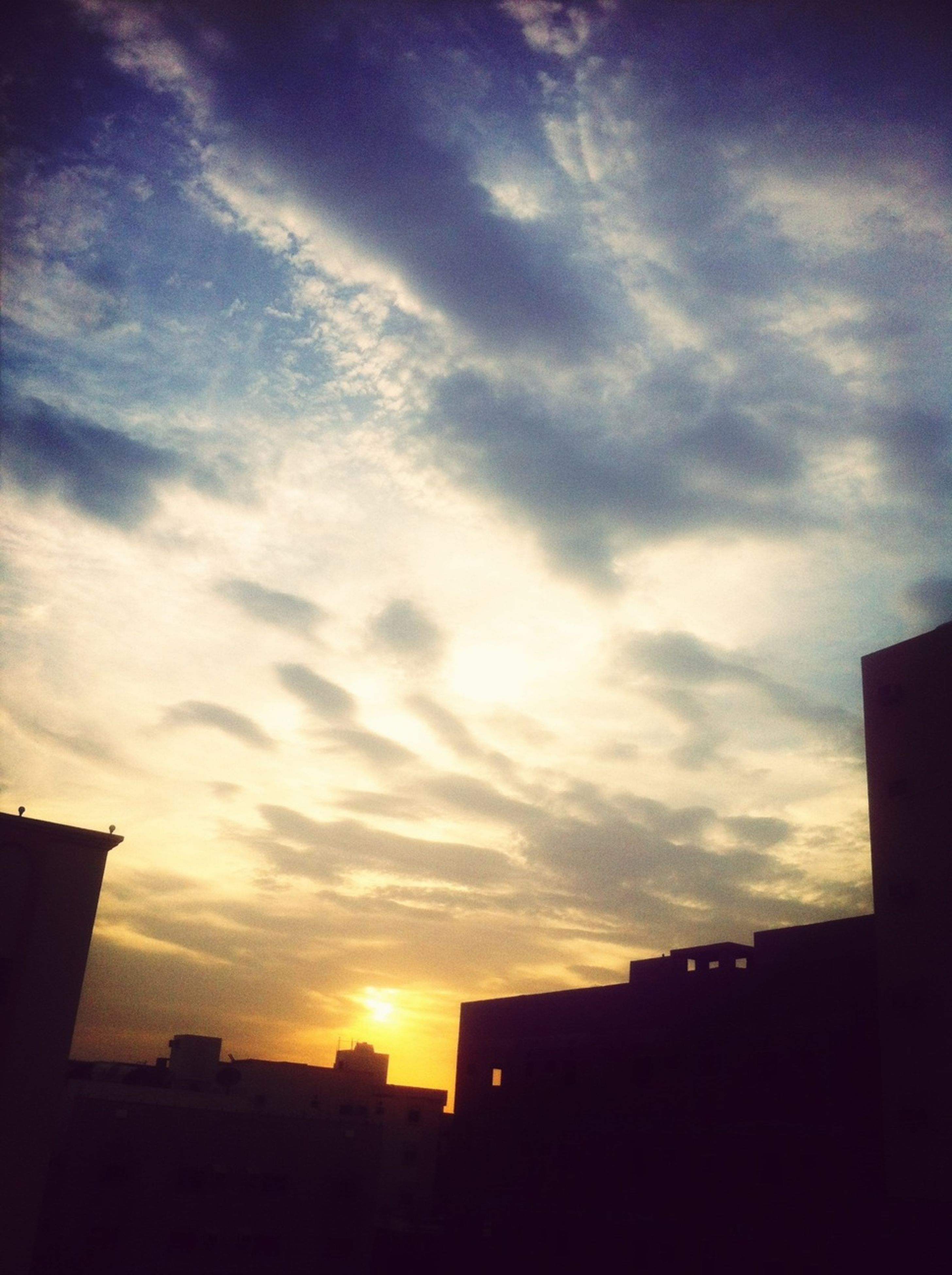 building exterior, architecture, built structure, sunset, silhouette, sky, cloud - sky, low angle view, residential structure, house, city, residential building, building, cloud, sunlight, outdoors, cloudy, orange color, nature, beauty in nature
