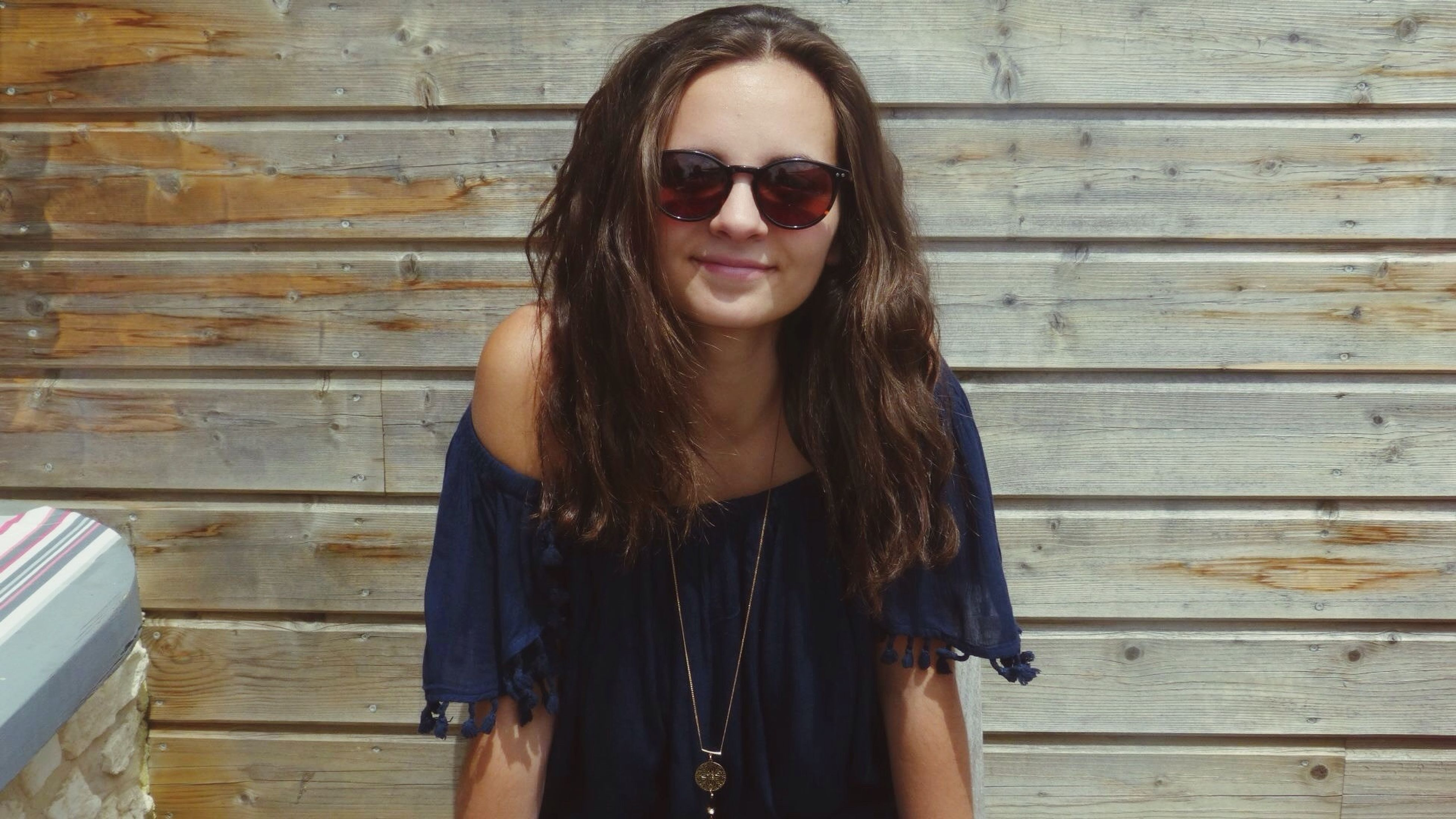 sunglasses, young adult, wood - material, one person, young women, standing, portrait, looking at camera, outdoors, beautiful woman, day, adult, people, adults only