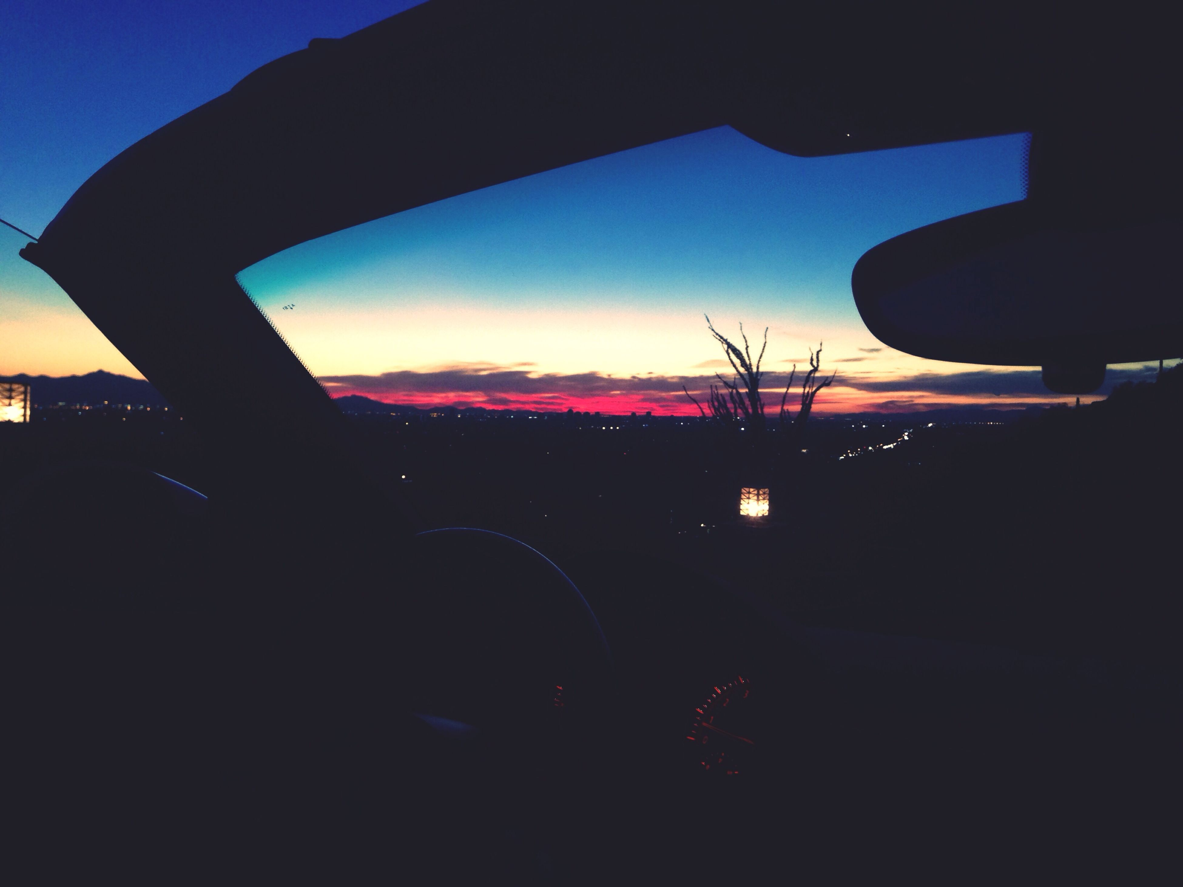 transportation, silhouette, land vehicle, car, sunset, mode of transport, sky, road, vehicle interior, dusk, street, travel, car interior, windshield, side-view mirror, dark, cloud, tree, on the move, cloud - sky