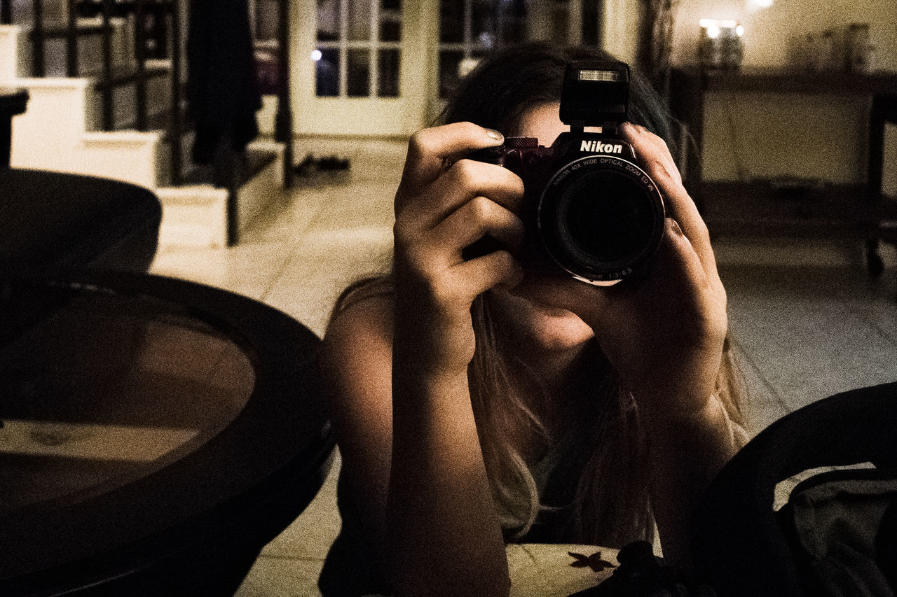 Camera Camera - Photographic Equipment Day Digital Camera Holding Human Body Part Human Hand Indoors  Leisure Activity Lifestyles Nikon One Person People Photo Photographer Photographing Photography Photography Themes Real People Shadow Sunlight Technology Women