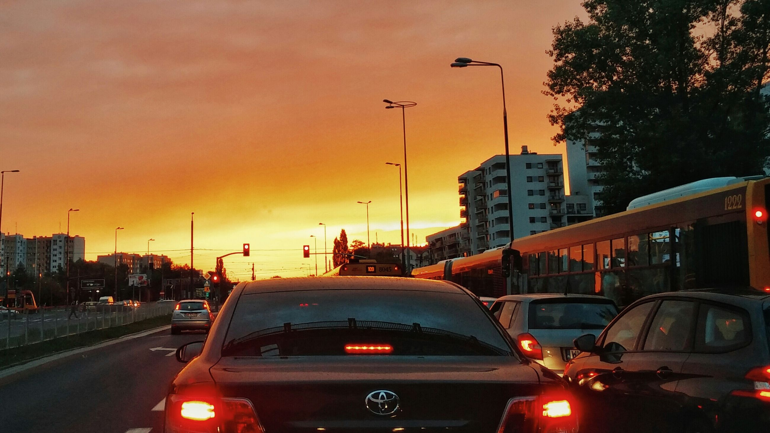 transportation, car, land vehicle, mode of transport, traffic, sunset, road, street, city, on the move, sky, street light, building exterior, architecture, illuminated, built structure, road marking, city street, travel, orange color