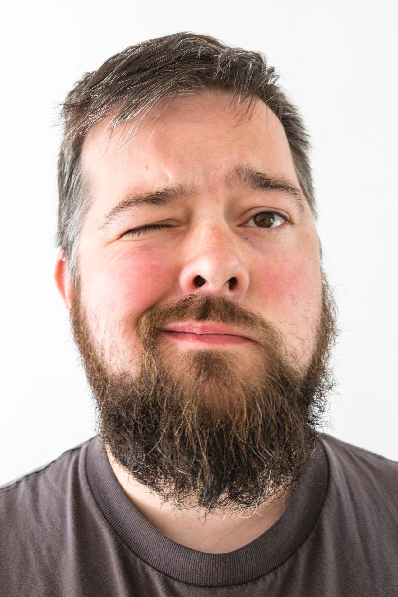 Adult Adults Only Beard Close-up Front View Headshot Human Body Part Human Face Indoors  Looking At Camera Males  Men One Man Only One Person Only Men People Portrait Smirk Studio Shot White Background Wink Young Adult