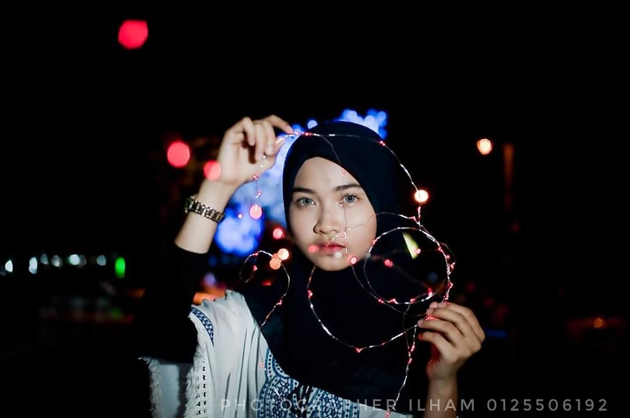night, one person, front view, illuminated, focus on foreground, young adult, real people, leisure activity, holding, beautiful woman, standing, headshot, one young woman only, young women, outdoors, lifestyles, portrait, one woman only, only women, city, adult, close-up, people, adults only