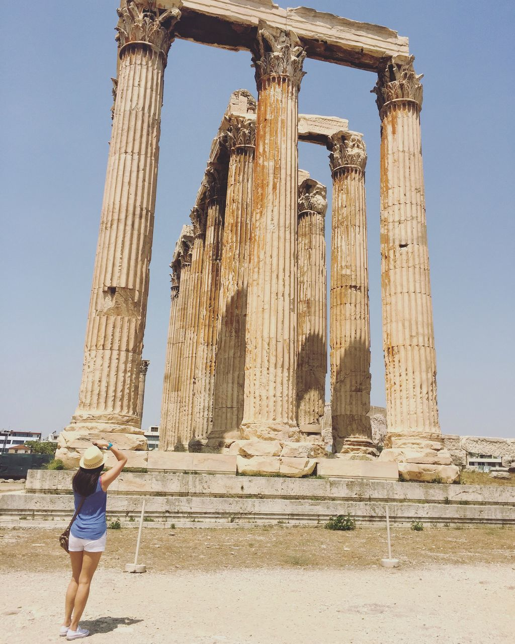 Woman Standing By Temple Of Olympian Zeus On Sunny Day