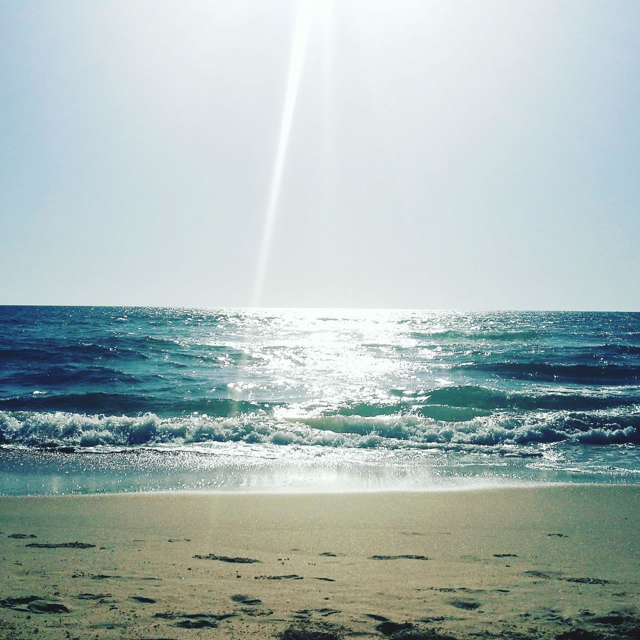 sea, horizon over water, beauty in nature, nature, water, scenics, beach, tranquility, tranquil scene, no people, idyllic, outdoors, sand, day, wave, sunlight, clear sky, sky, vapor trail