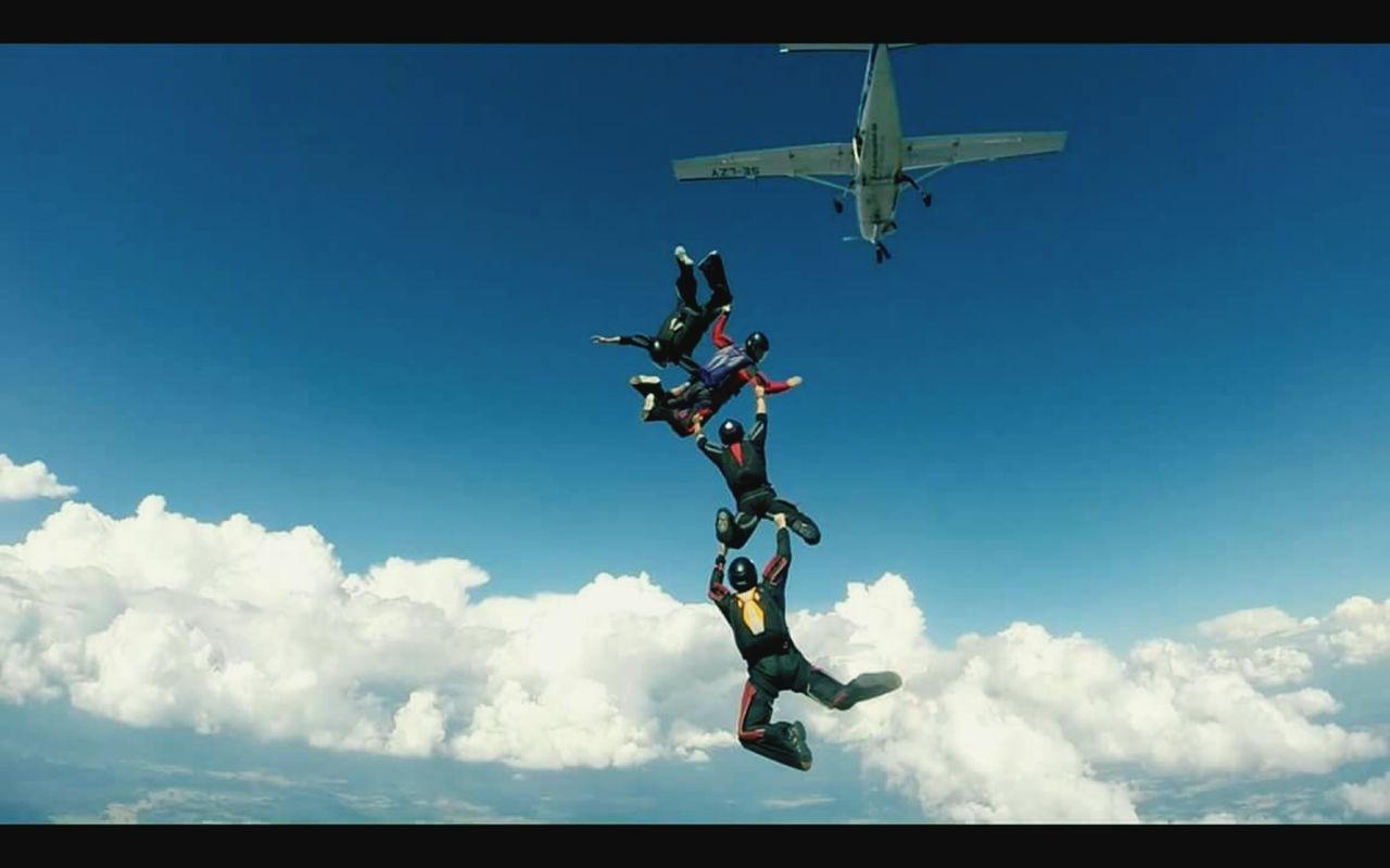 mid-air, sky, day, flying, low angle view, outdoors, extreme sports, skydiving, cloud - sky, blue, risk, airplane, jumping, men, stunt, adventure, togetherness, parachute, airshow, teamwork, people