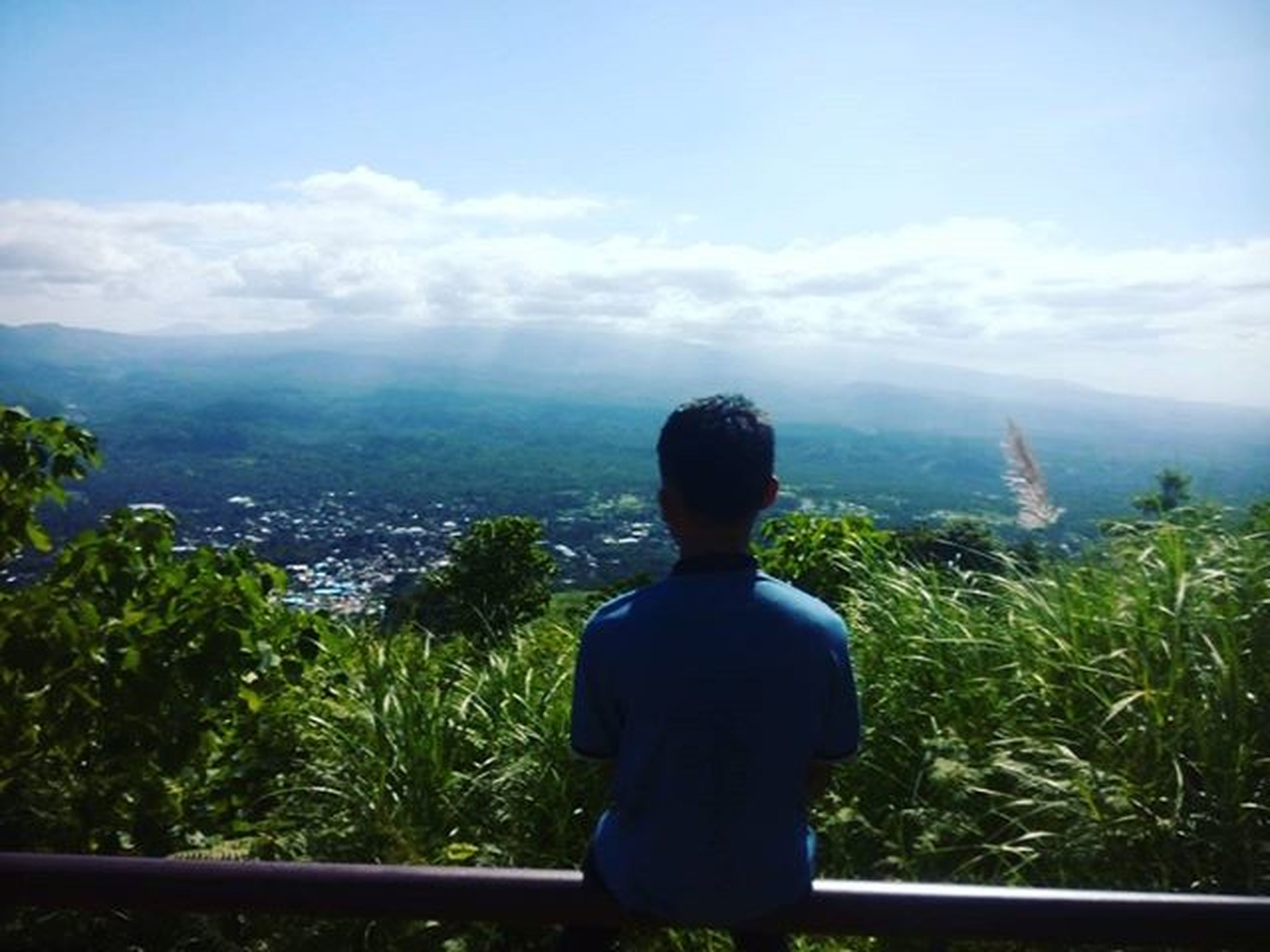 rear view, sky, mountain, lifestyles, leisure activity, looking at view, standing, nature, tranquility, beauty in nature, landscape, three quarter length, tranquil scene, scenics, cloud - sky, casual clothing, waist up, tree