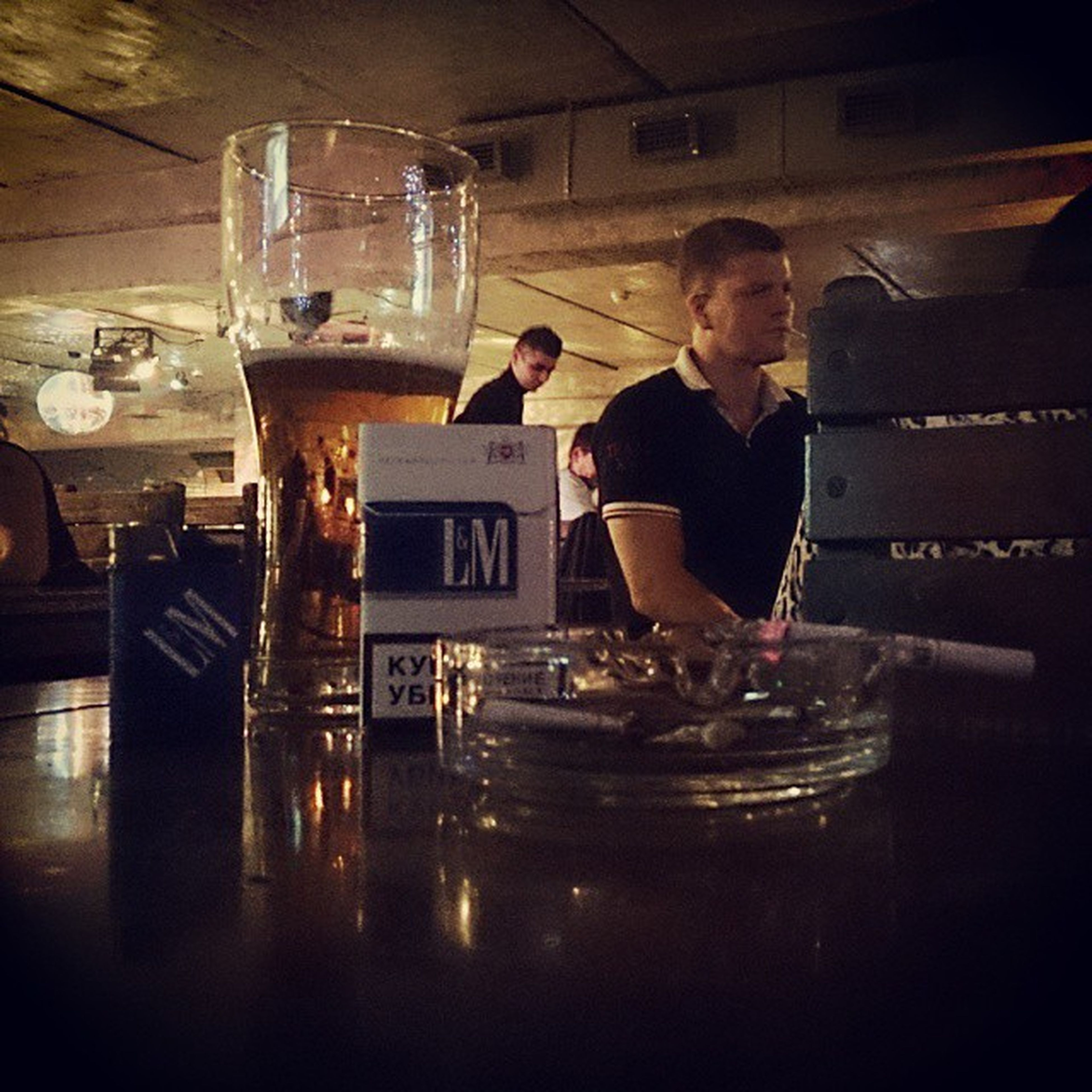indoors, food and drink, drink, lifestyles, refreshment, table, young men, holding, person, leisure activity, restaurant, drinking glass, alcohol, sitting, casual clothing, men, freshness