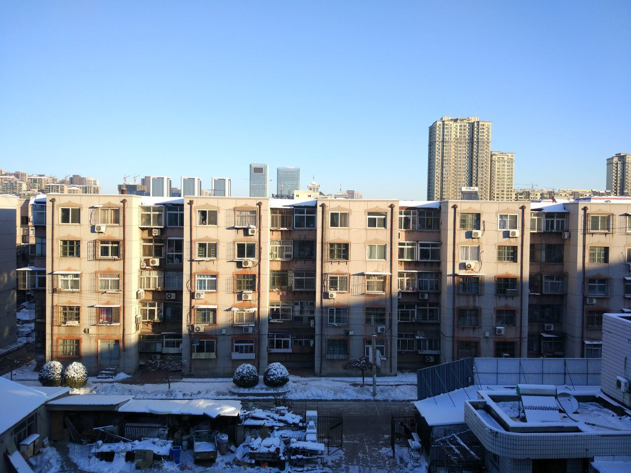 building exterior, architecture, built structure, clear sky, day, outdoors, cold temperature, winter, snow, city, no people, cityscape, skyscraper, sky