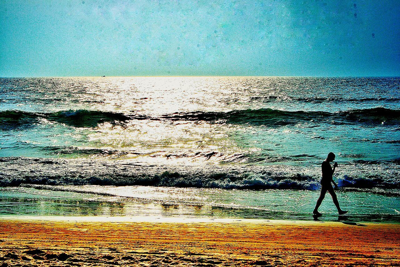 Side View Of Man Walking On Shore At Beach Against Sky During Sunny Day
